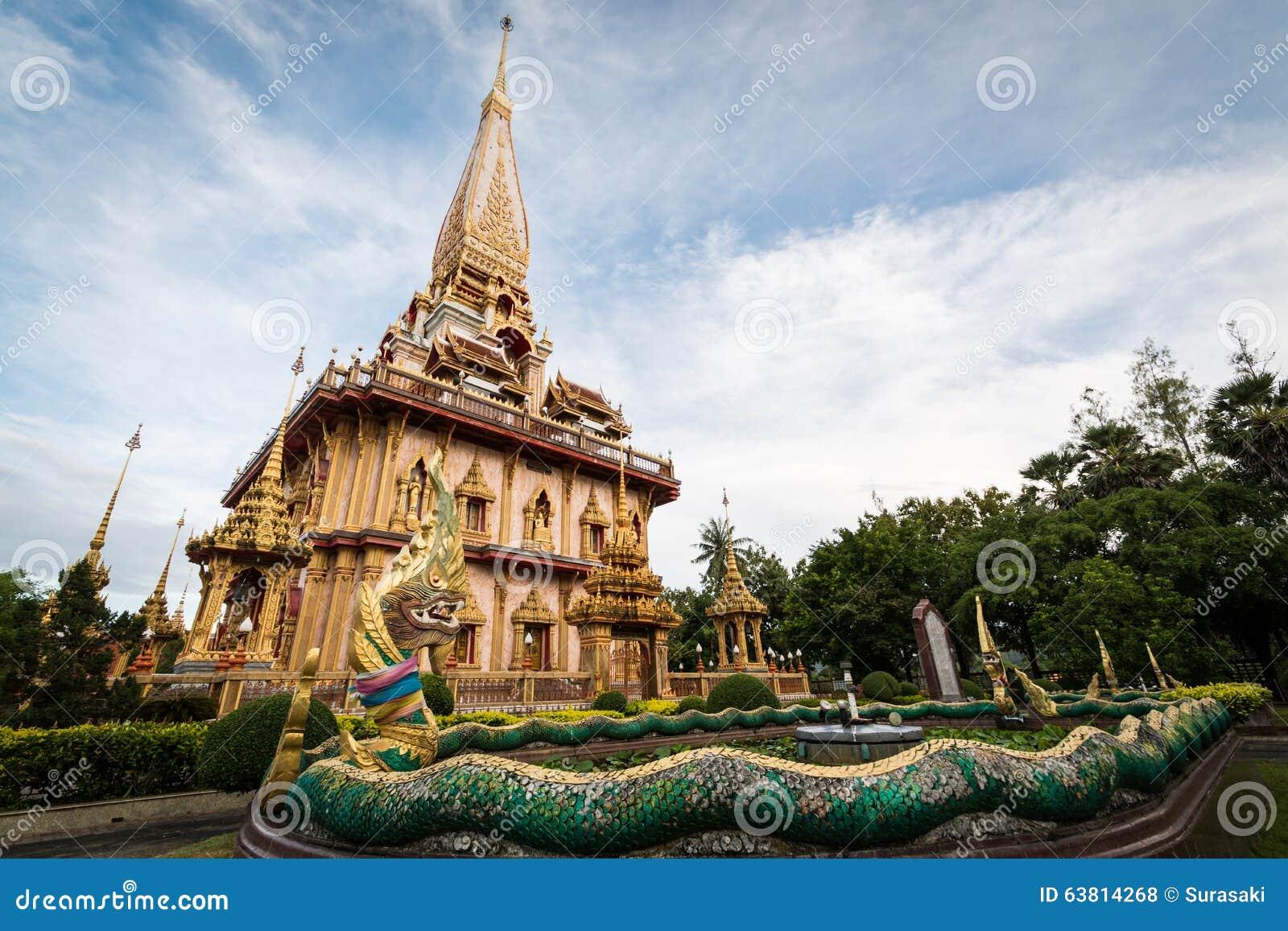 Escultura do Naga no jardim com o pagode santamente do templo do chalong