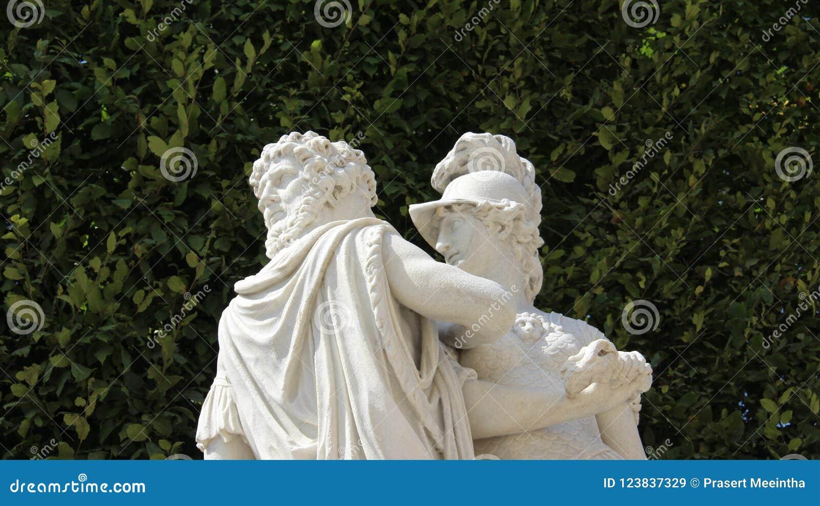 A escultura romântica do amor com verde cerca fundos