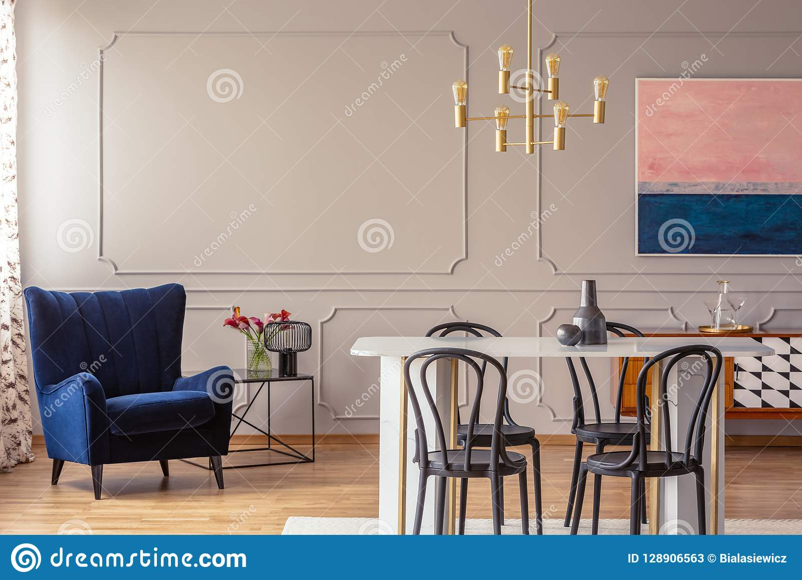 Escuro - poltrona azul em um interior da sala de jantar com uma tabela, umas cadeiras e uma lâmpada dourada