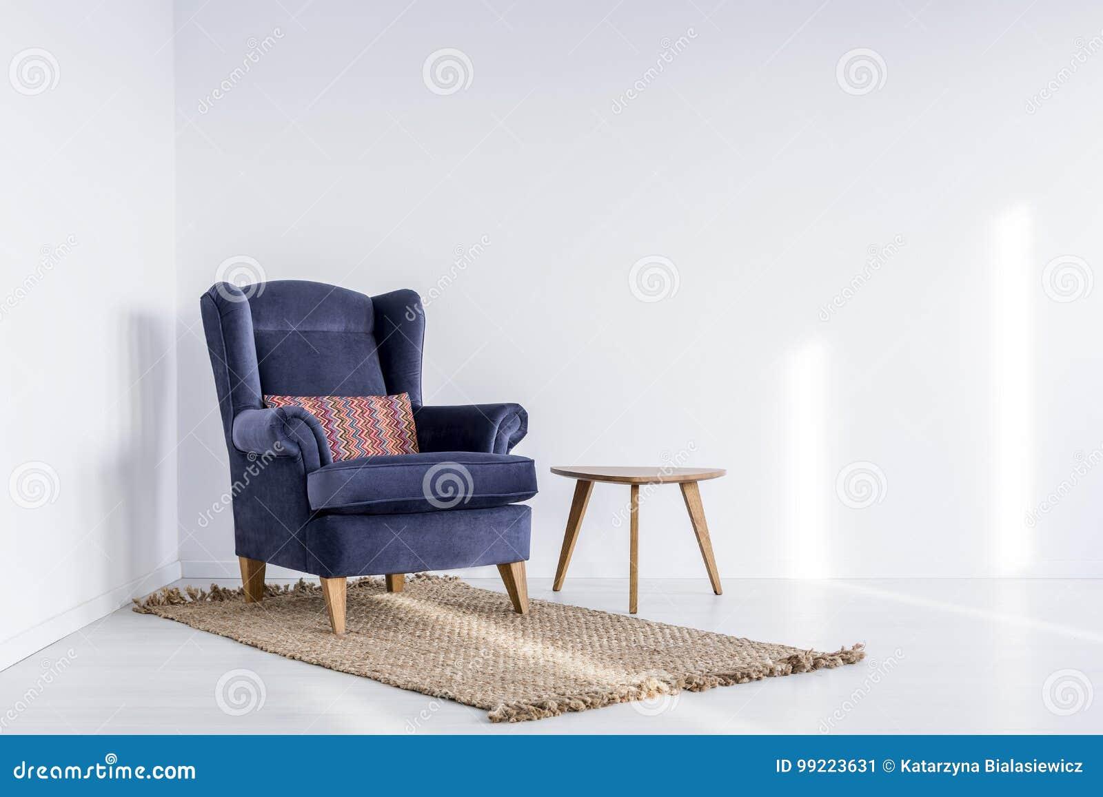 Escuro - poltrona azul no tapete marrom
