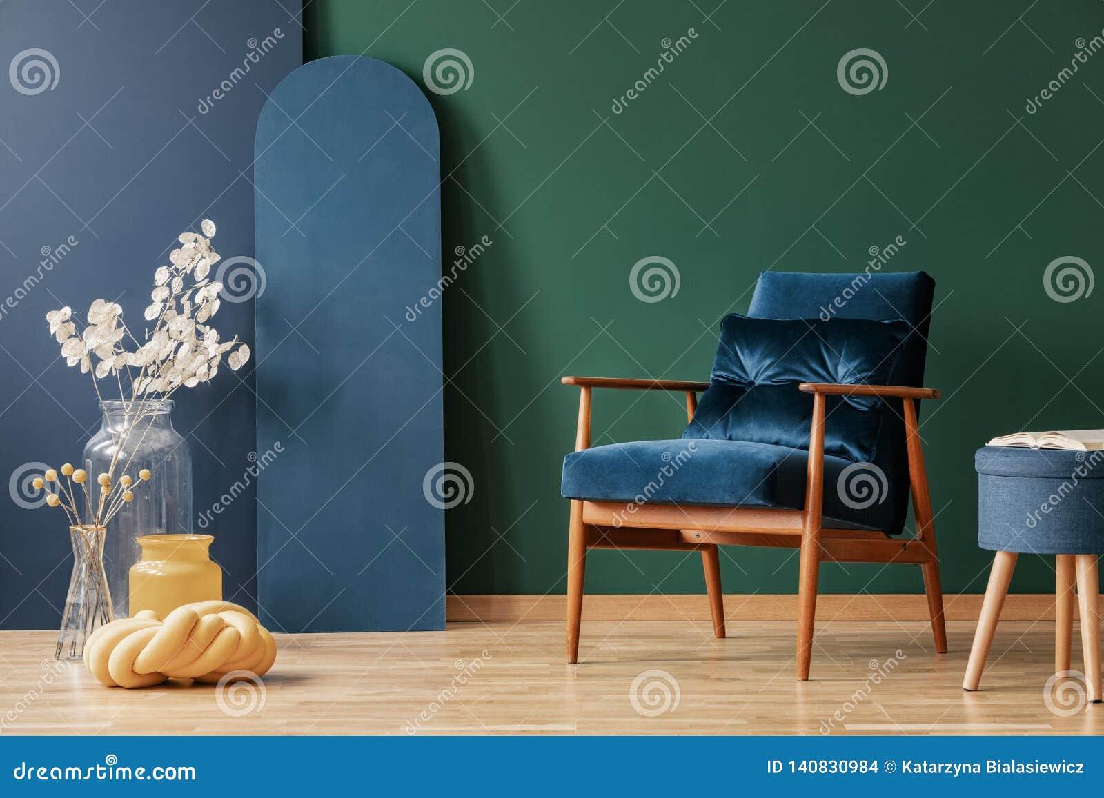 Escuro retro - poltrona azul em elegante, sala de visitas interior com espaço da cópia na parede verde e azul vazia