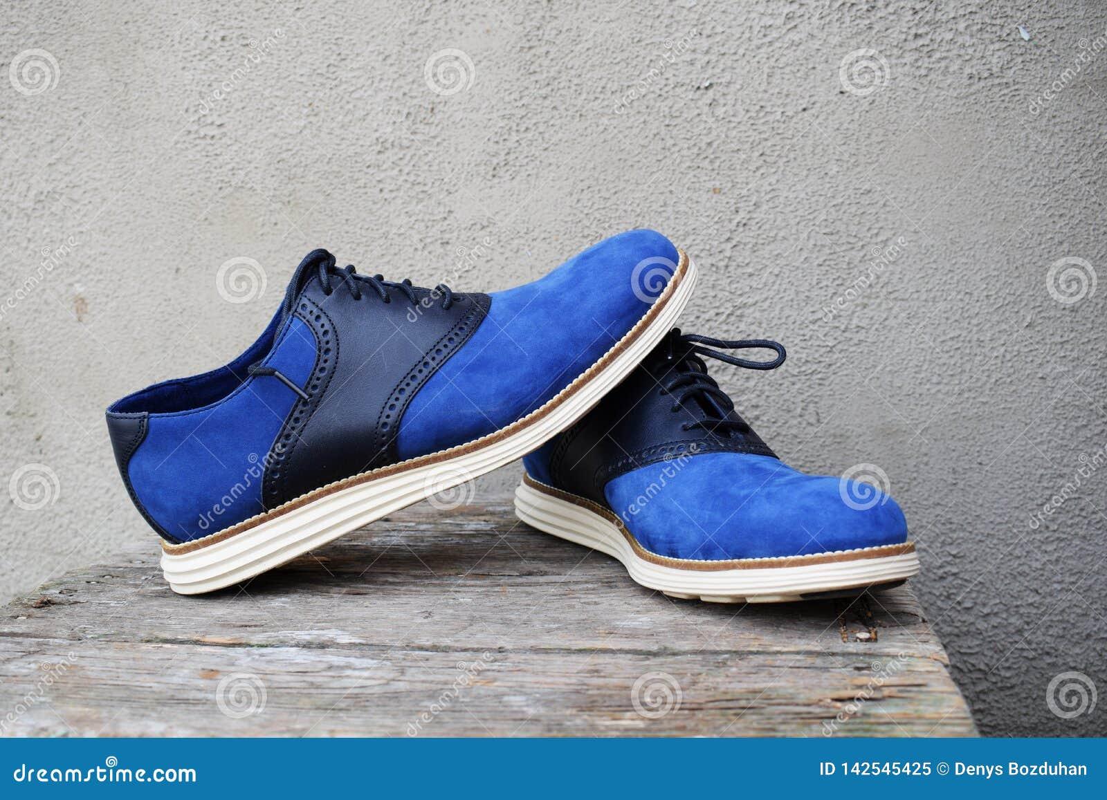 Escuro - sapatilhas azuis com uma sola branca em um fundo de madeira