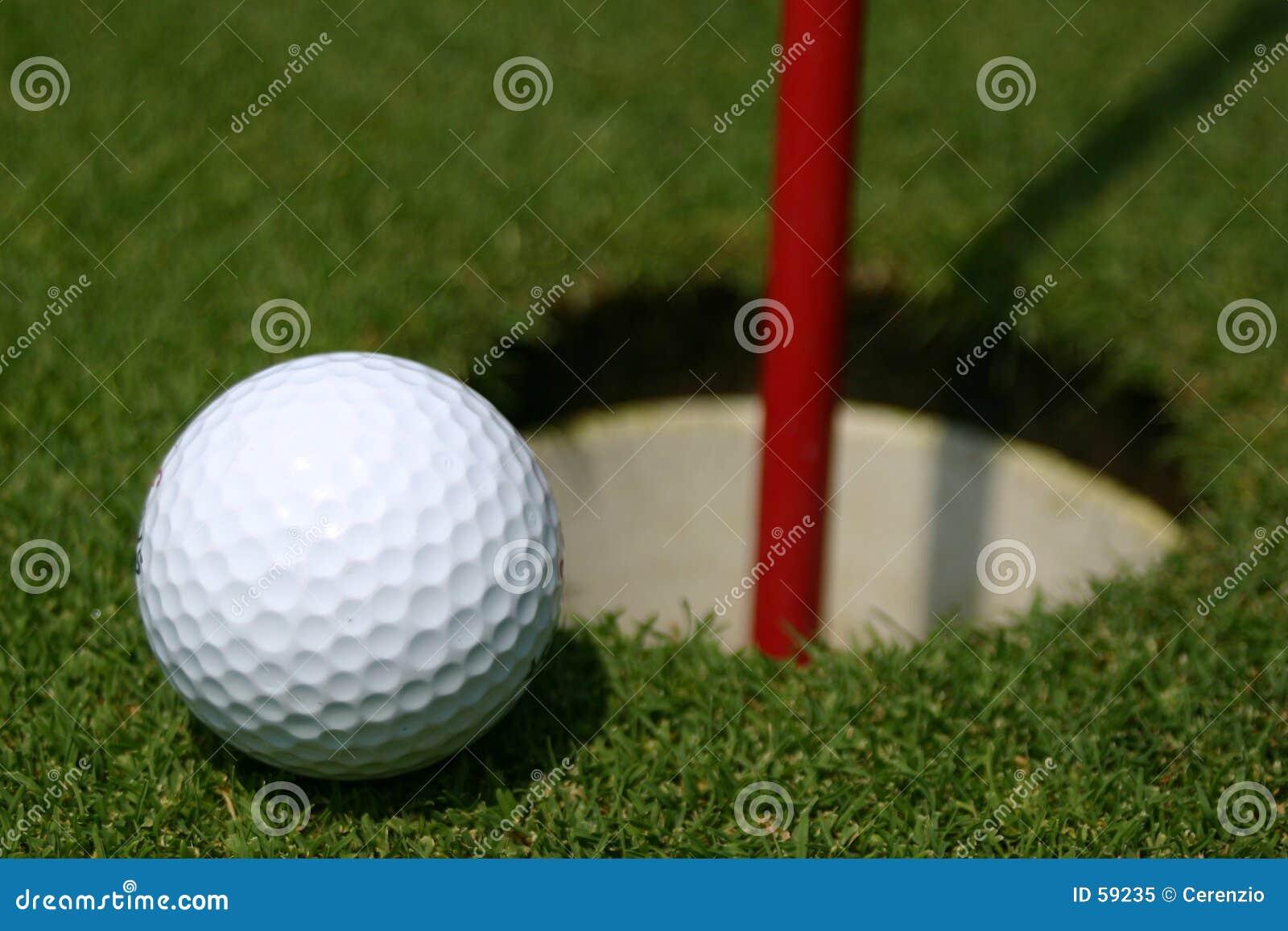 Esfera de golfe no furo da prática