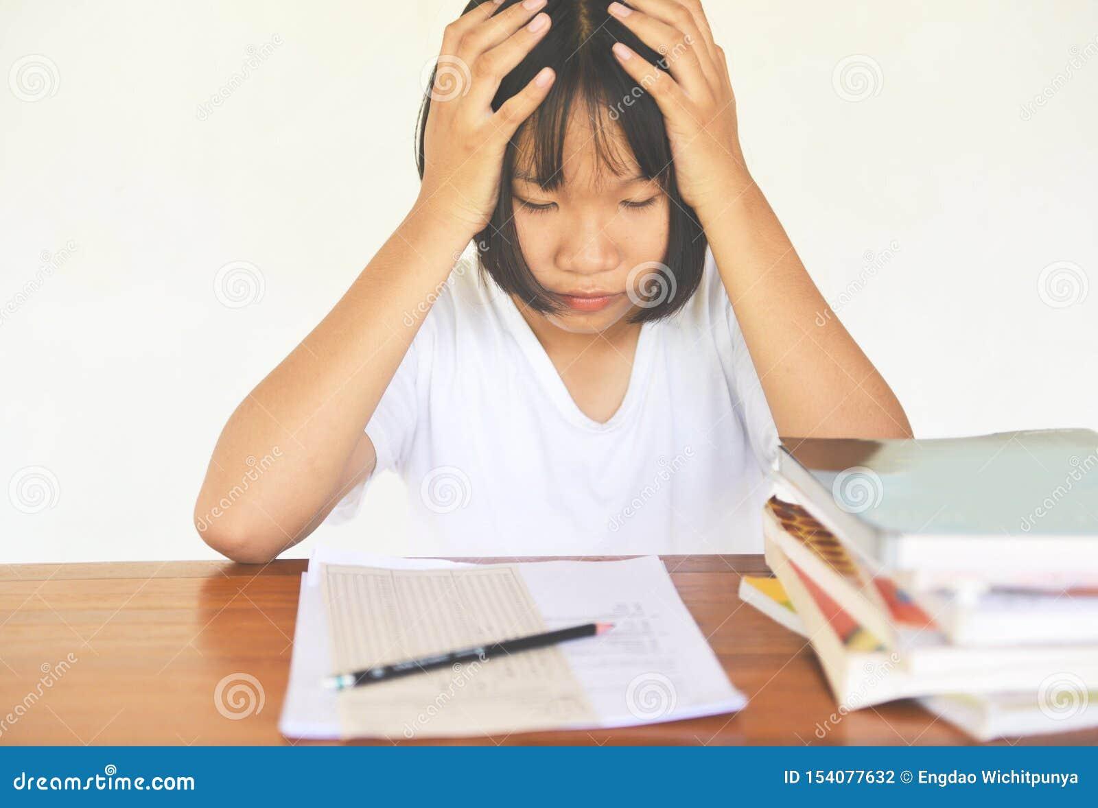 Esforço do exame - a faculdade fêmea nova da educação na classe que toma notas e que usa um lápis que senta-se aprendendo o conce