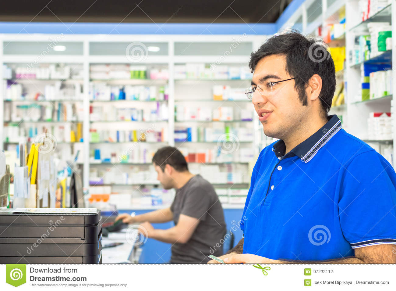 Eskisehir, Turkey - June 14, 2017: Portrait of a young male pharmacist standing at counter in pharmacy.