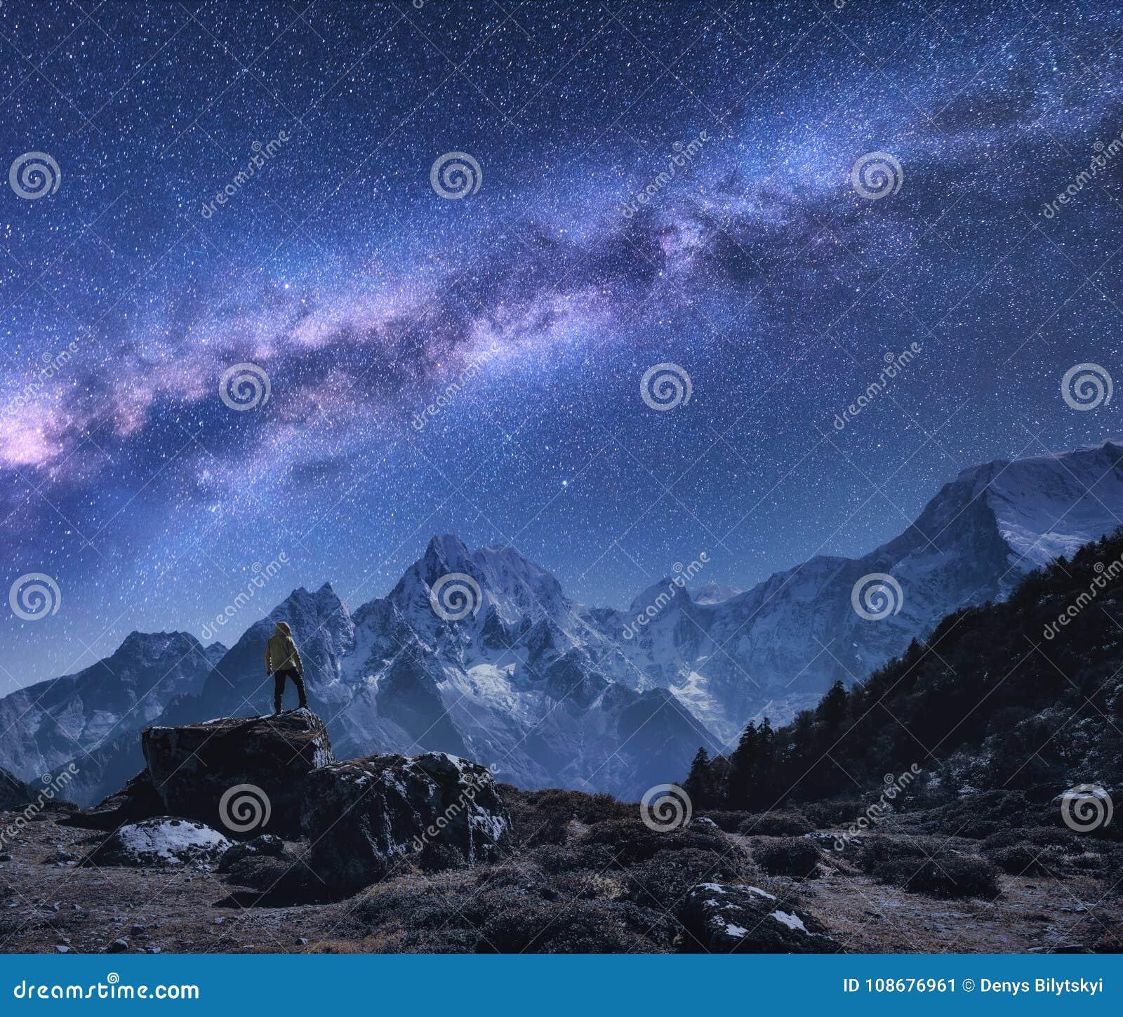 Espaço com Via Látea, homem na pedra e montanhas