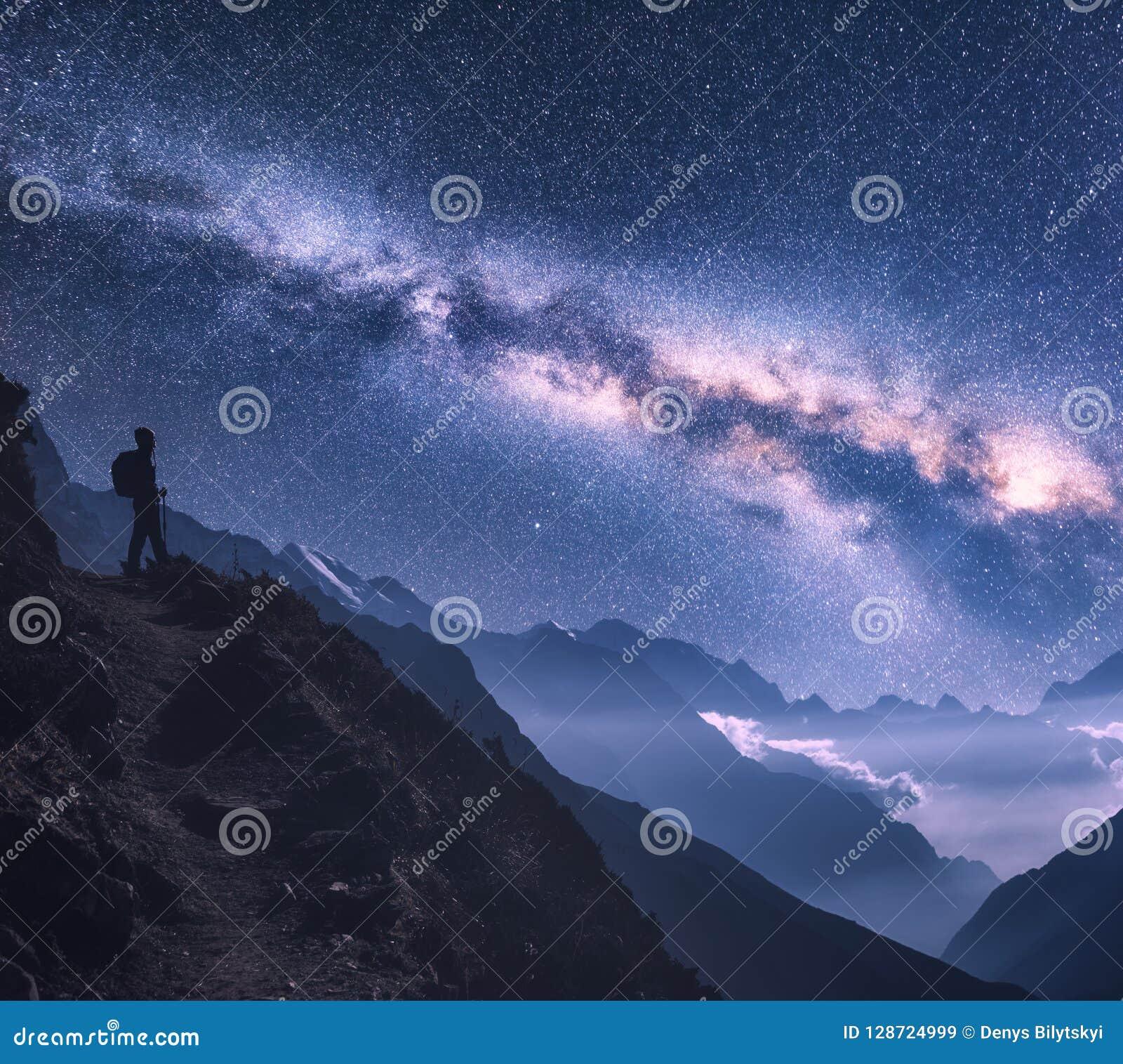 Espaço com Via Látea, menina e montanhas na noite