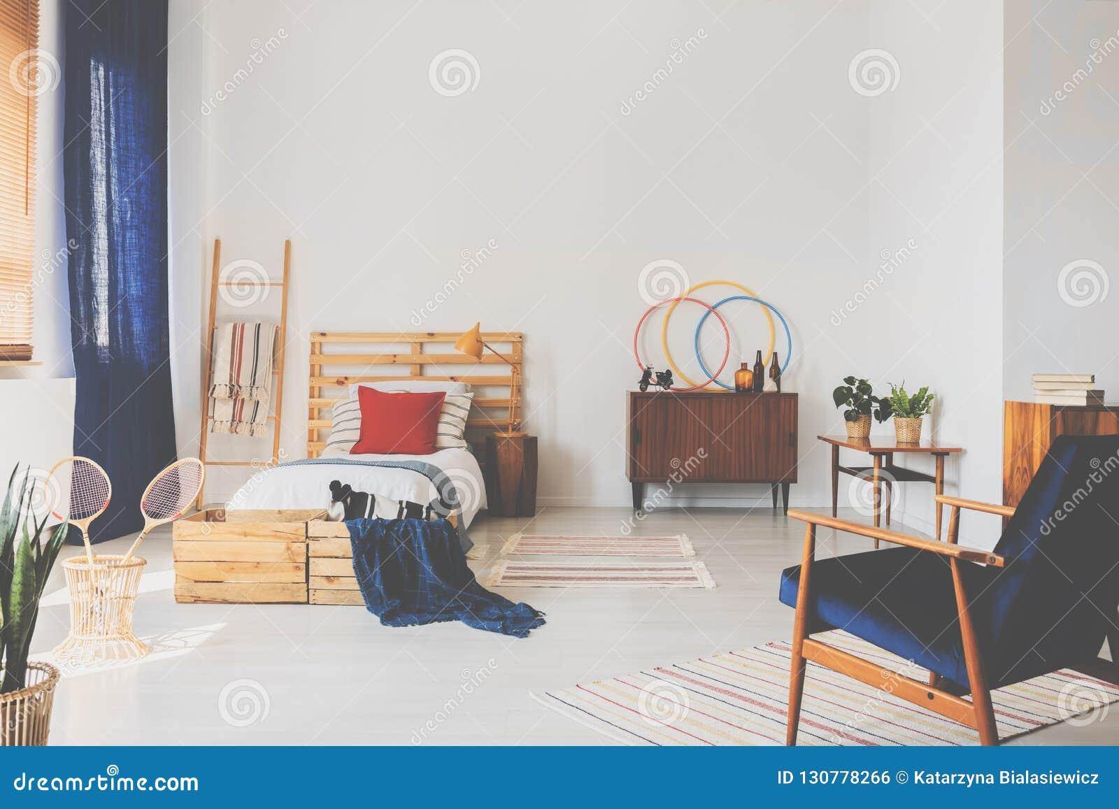 Espaço da cópia na parede branca do quarto do adolescente do oldschool com mobília de madeira e escuro - acentos azuis