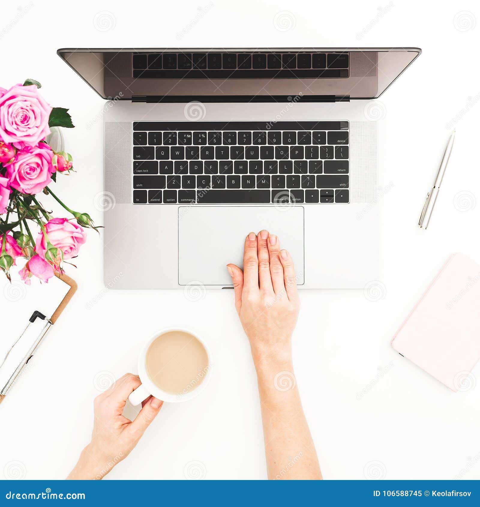 Espaço de trabalho com mãos fêmeas, portátil da mulher, ramalhete cor-de-rosa das rosas, caneca de café, diário Vista superior Me