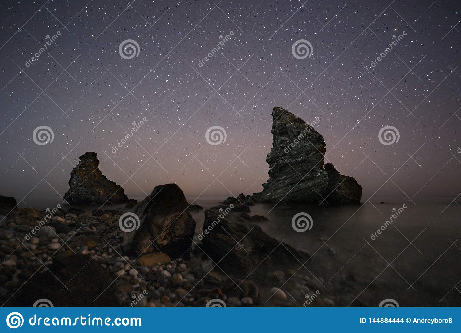 España, Málaga, Nerja, Molino de Papel: Noche estrellada en la playa con las rocas