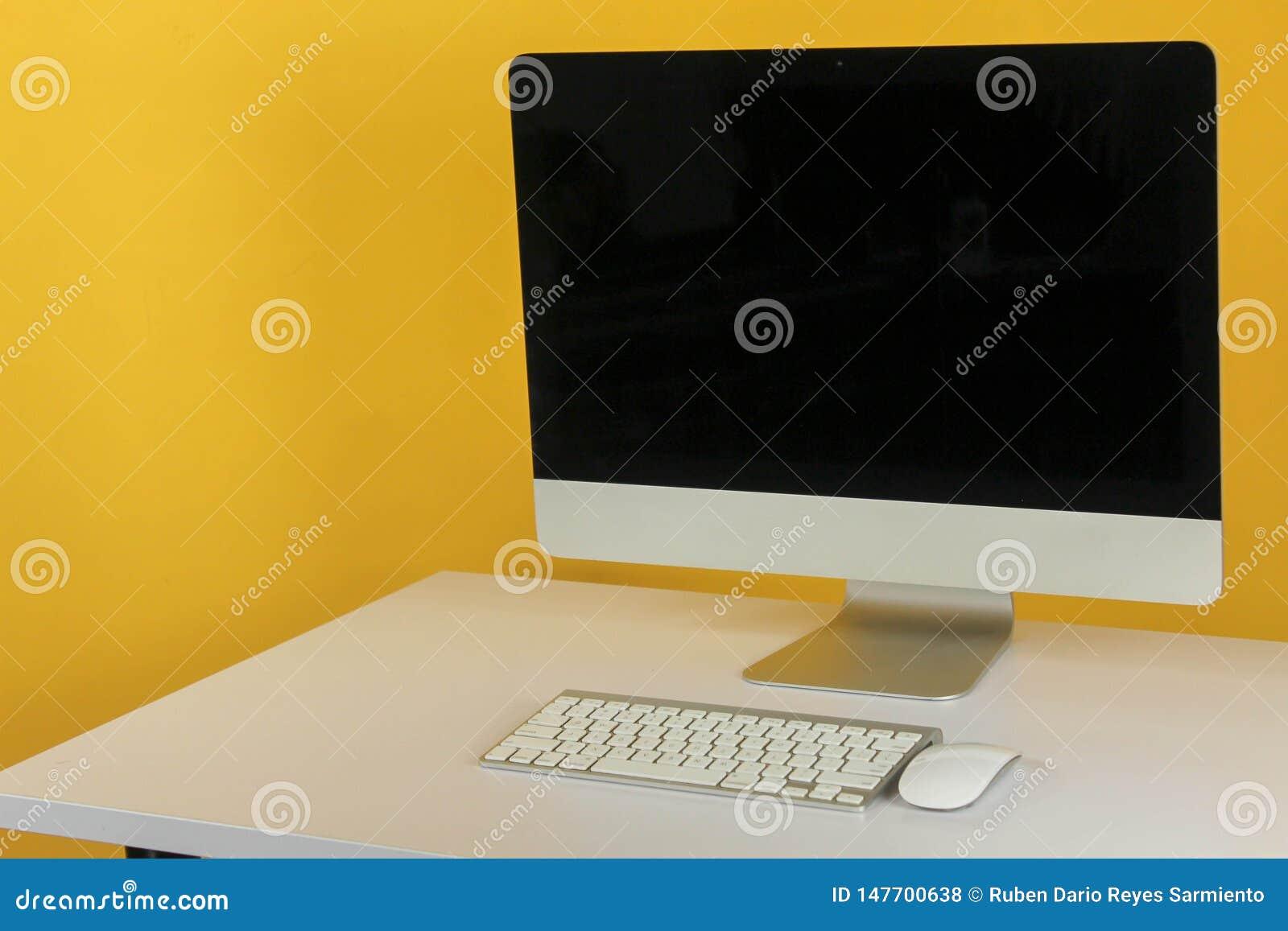 Espa?o de trabalho com o computador na casa ou no est?dio, amarelo da parede do fundo