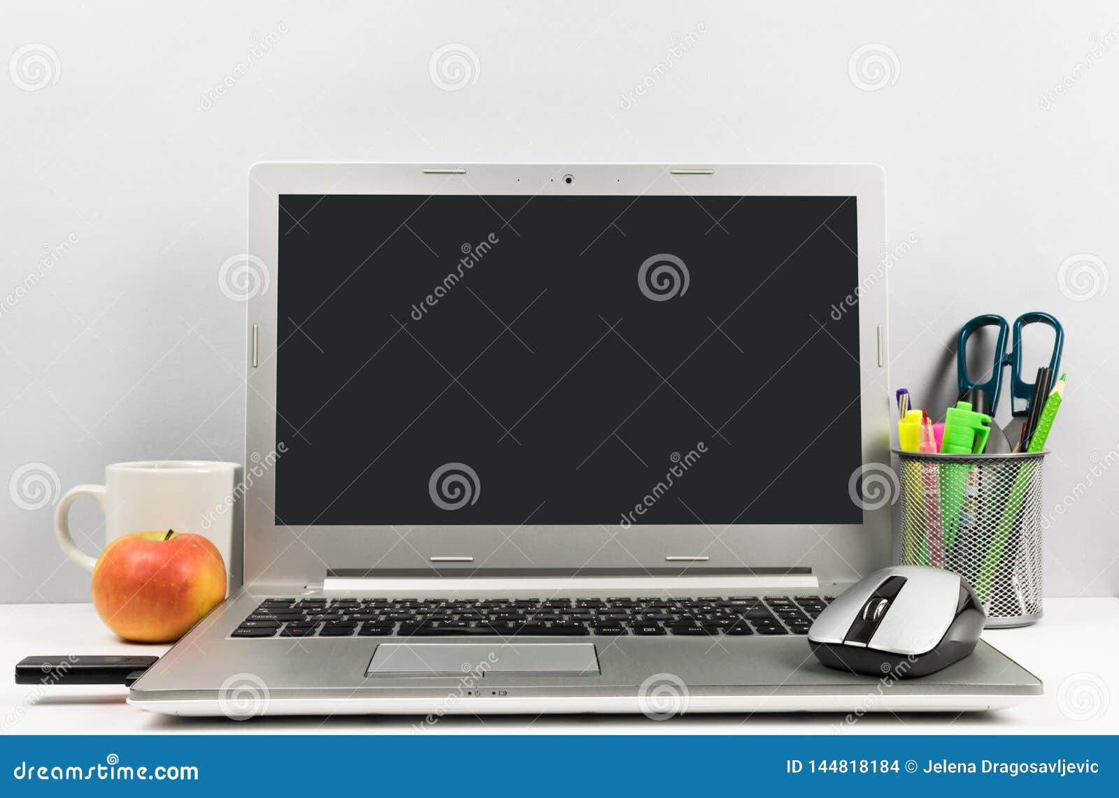 Espace de travail avec l ordinateur portable, l écran noir, la tasse de café, la pomme, l éclair d USB, et le plumier