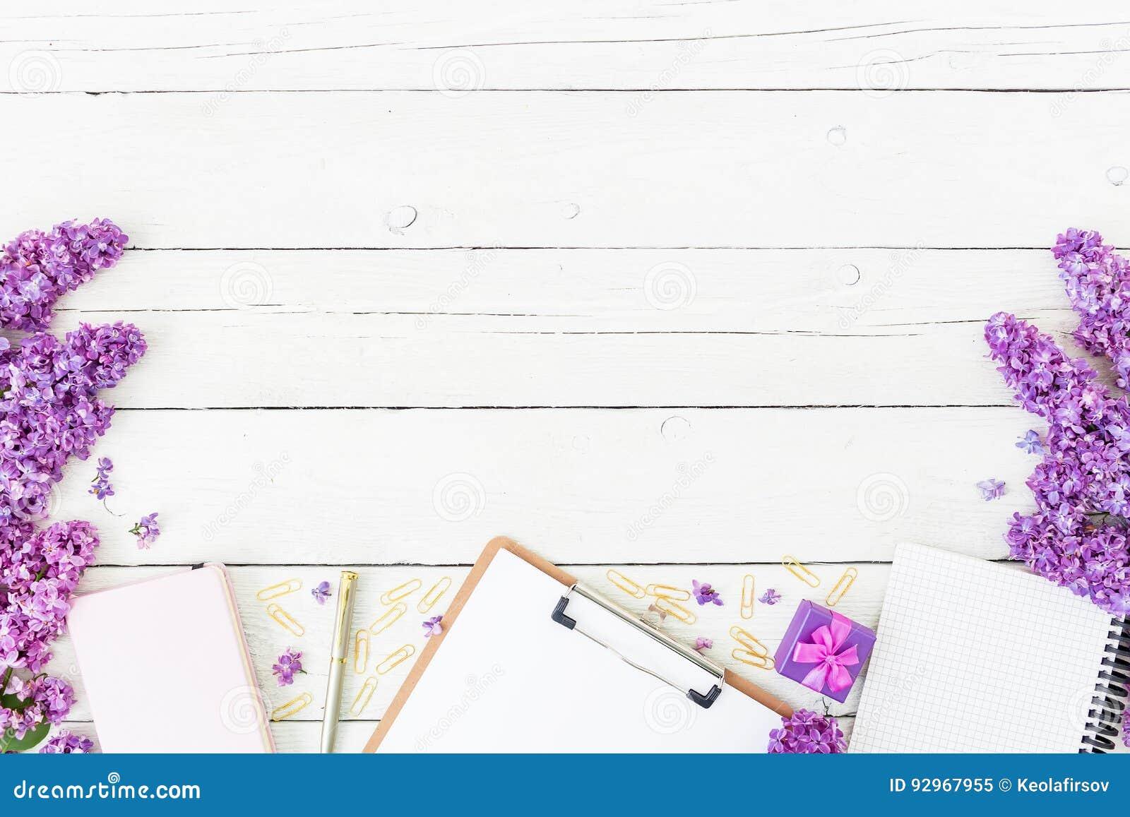 Espace de travail de Blogger ou d indépendant avec le presse-papiers, le carnet, le stylo, le lilas, la boîte et les pétales sur