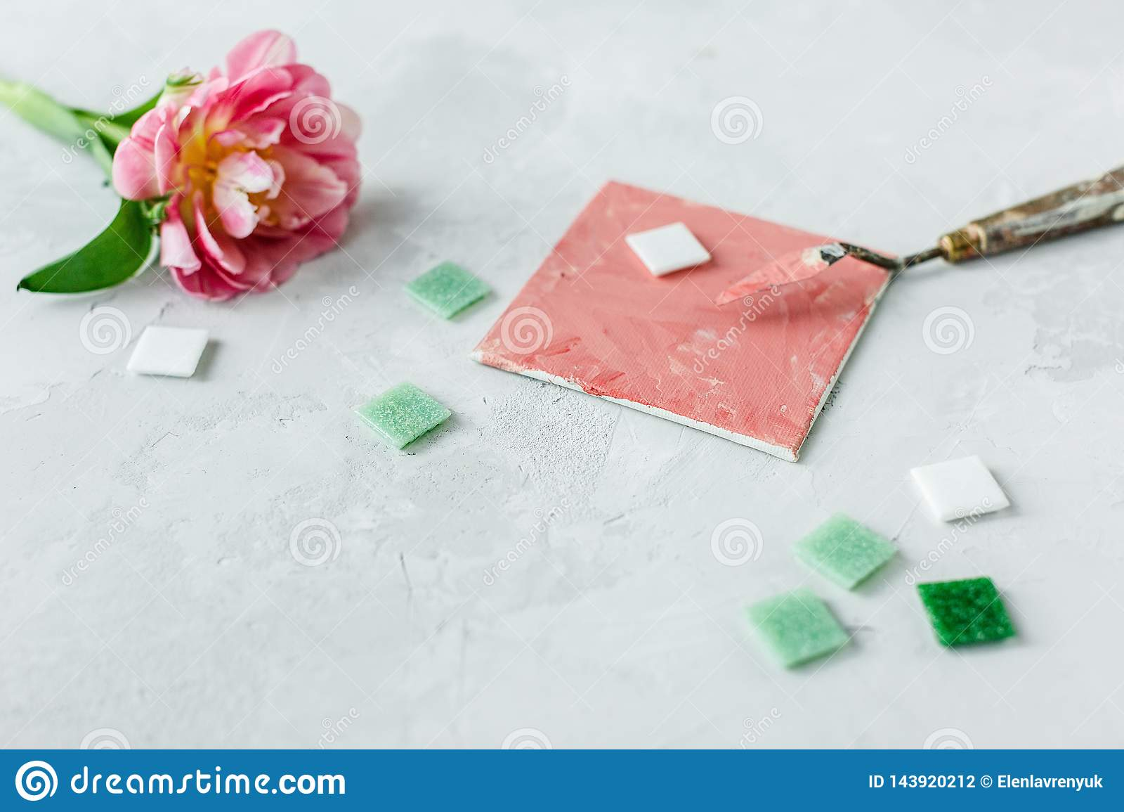 Espacio de trabajo con el cuchillo de paleta, la pintura de la lona, la flor del tulipán y el mosaico en backround gris