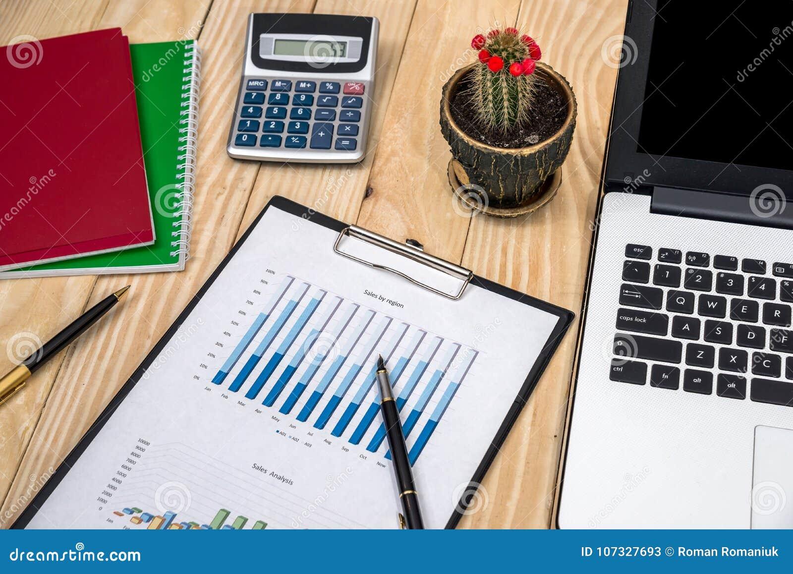 Espacio de trabajo con el gráfico, el ordenador y otros herramientas