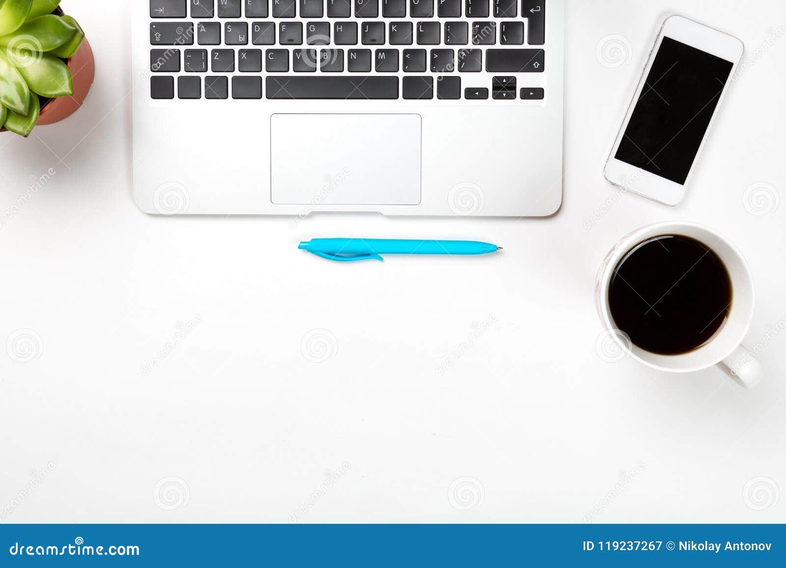 Espacio de trabajo conceptual o concepto del negocio Ordenador portátil con la planta en un pote, la taza de pluma azul del café