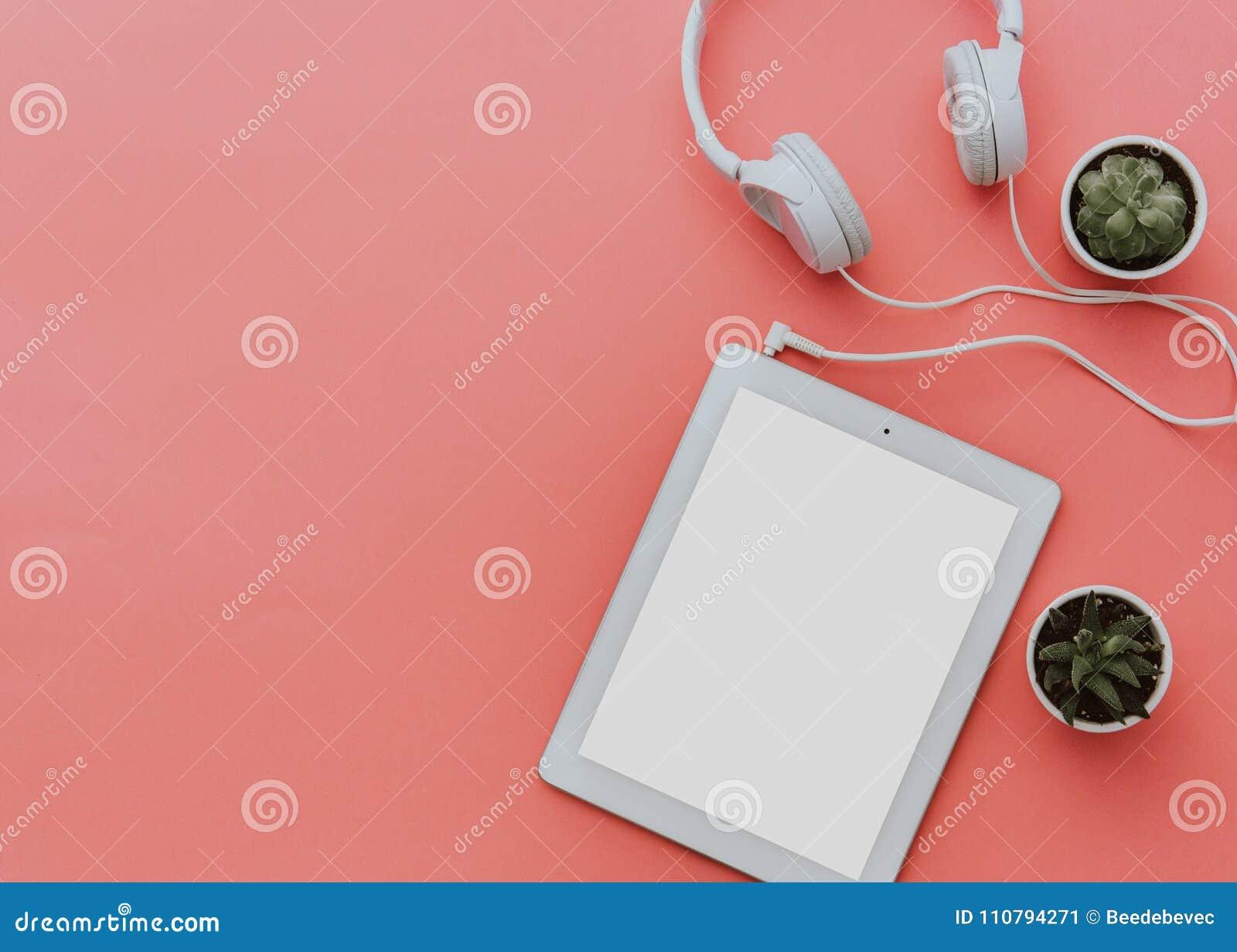 Espacio de trabajo del Blogger con la tableta y los auriculares en fondo en colores pastel Imite para arriba, endecha del plano,