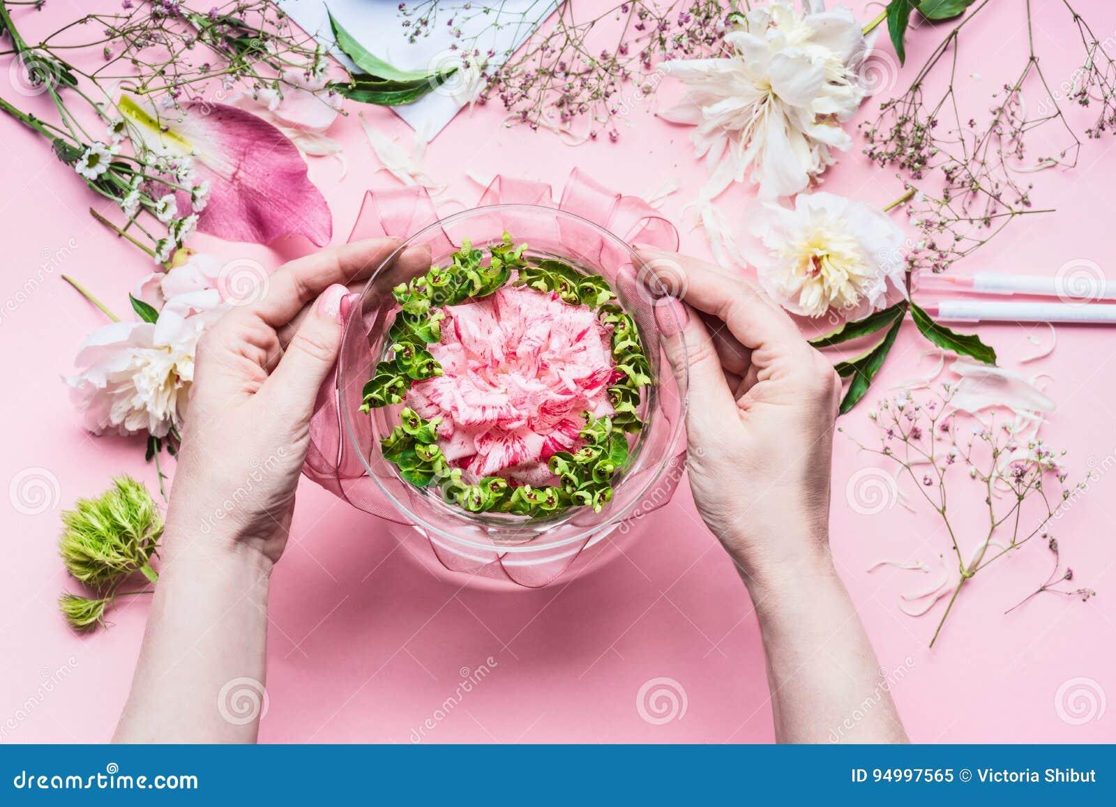 Espacio de trabajo rosado del florista con los lirios y otras flores, florero de cristal con agua Manos femeninas que hacen centr