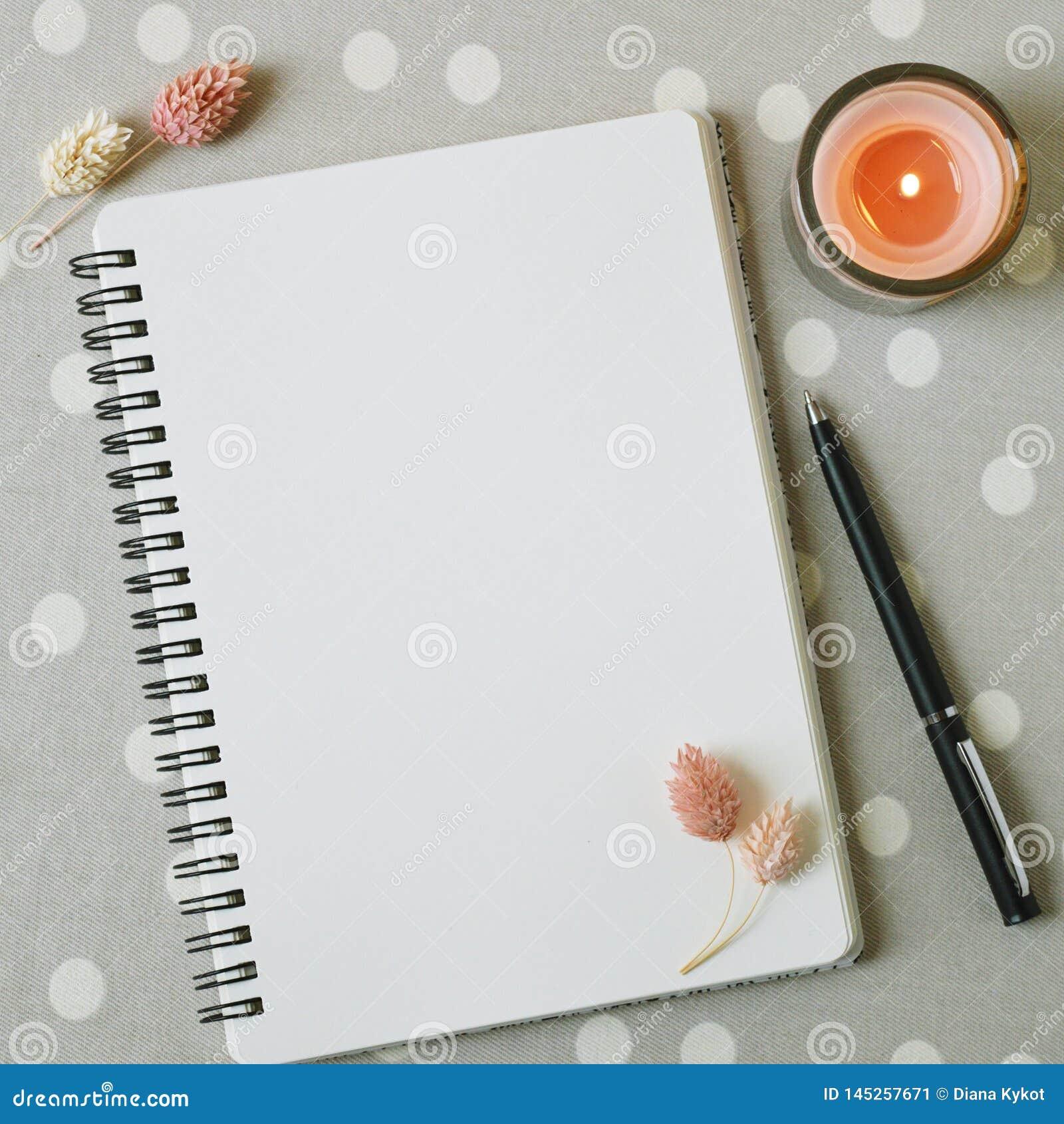 Espacio en blanco de la p?gina blanca del cuaderno, de flores rosadas secadas y de la vela coralina