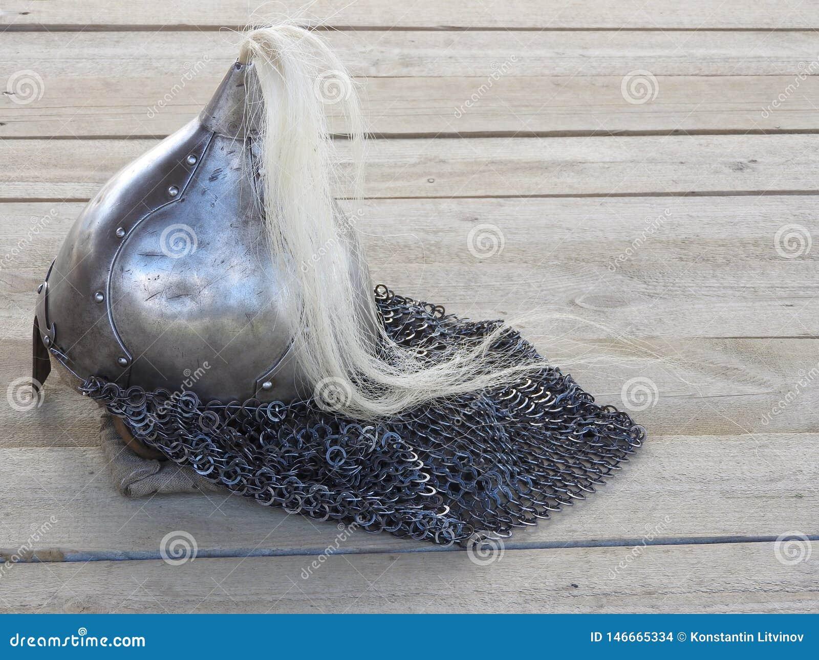 Espada, armadura de corrente e o capacete do soldado com chifres em um fundo de madeira com luz bonita