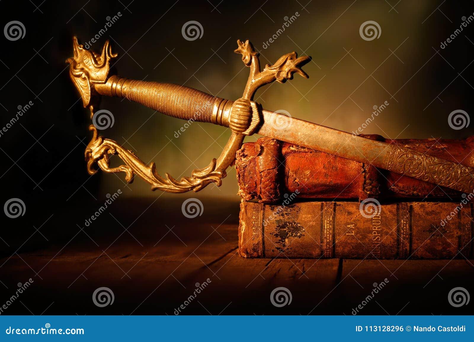Espada velha com os livros de couro na tabela de madeira