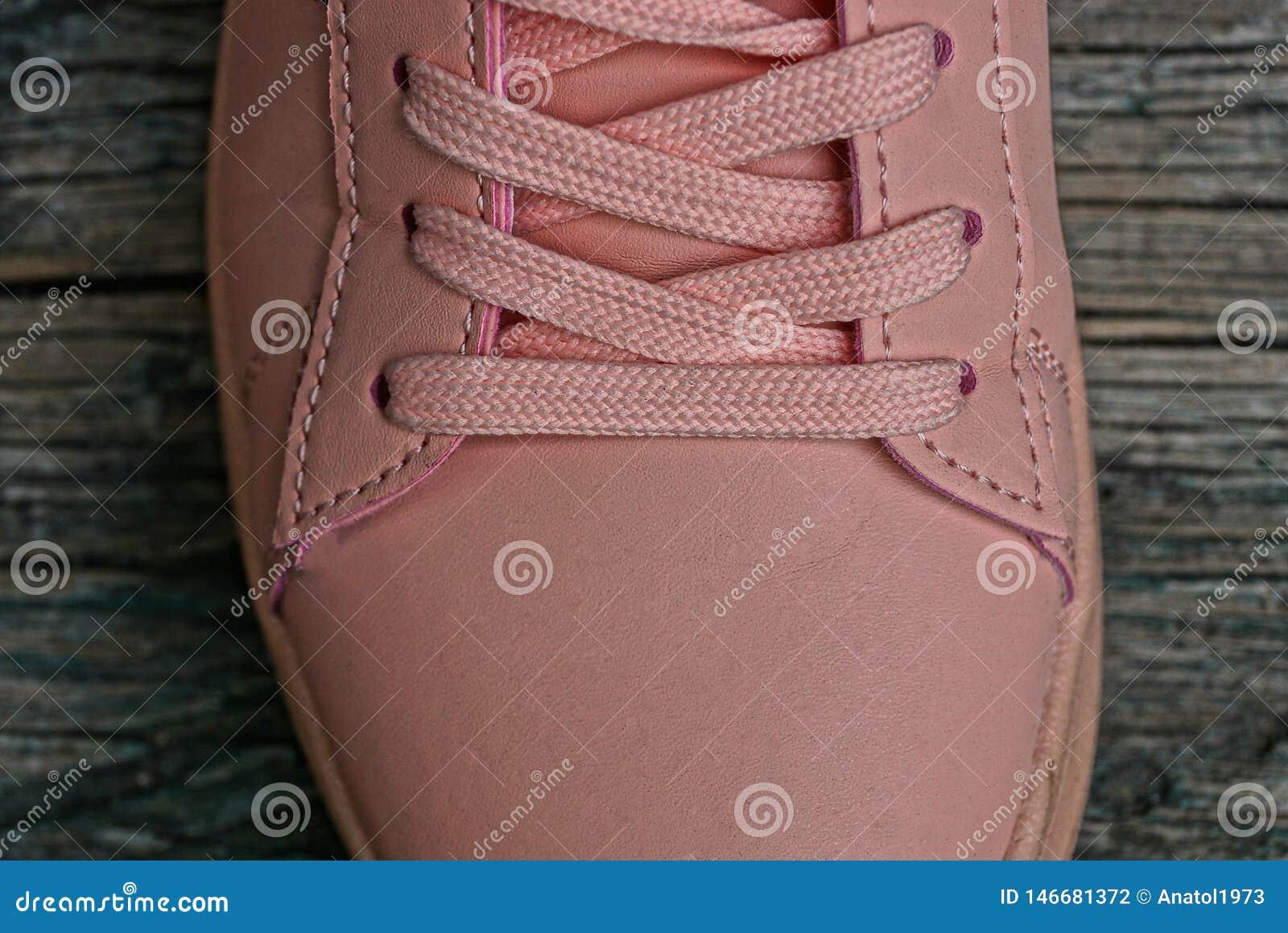Espadrille en cuir rose avec le cordon sur la table grise
