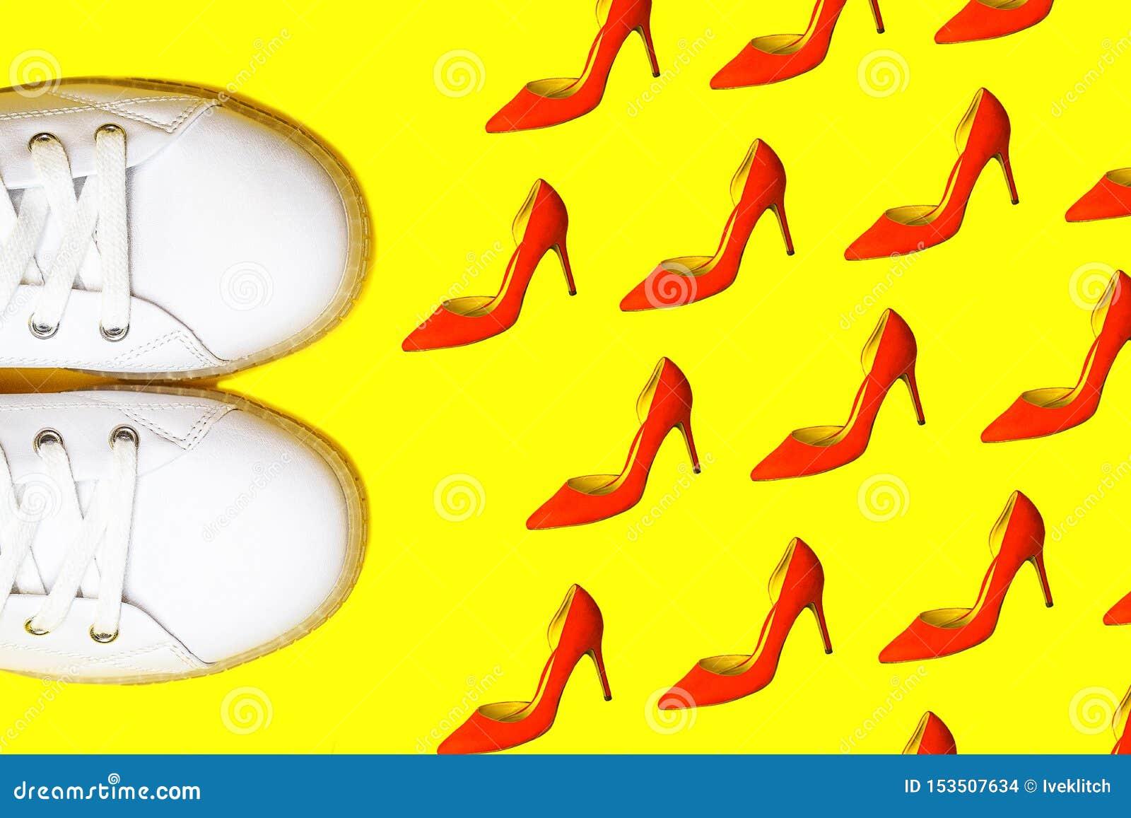 Espadrilles blanches de mode contre le modèle rouge femelle de chaussures sur le fond jaune