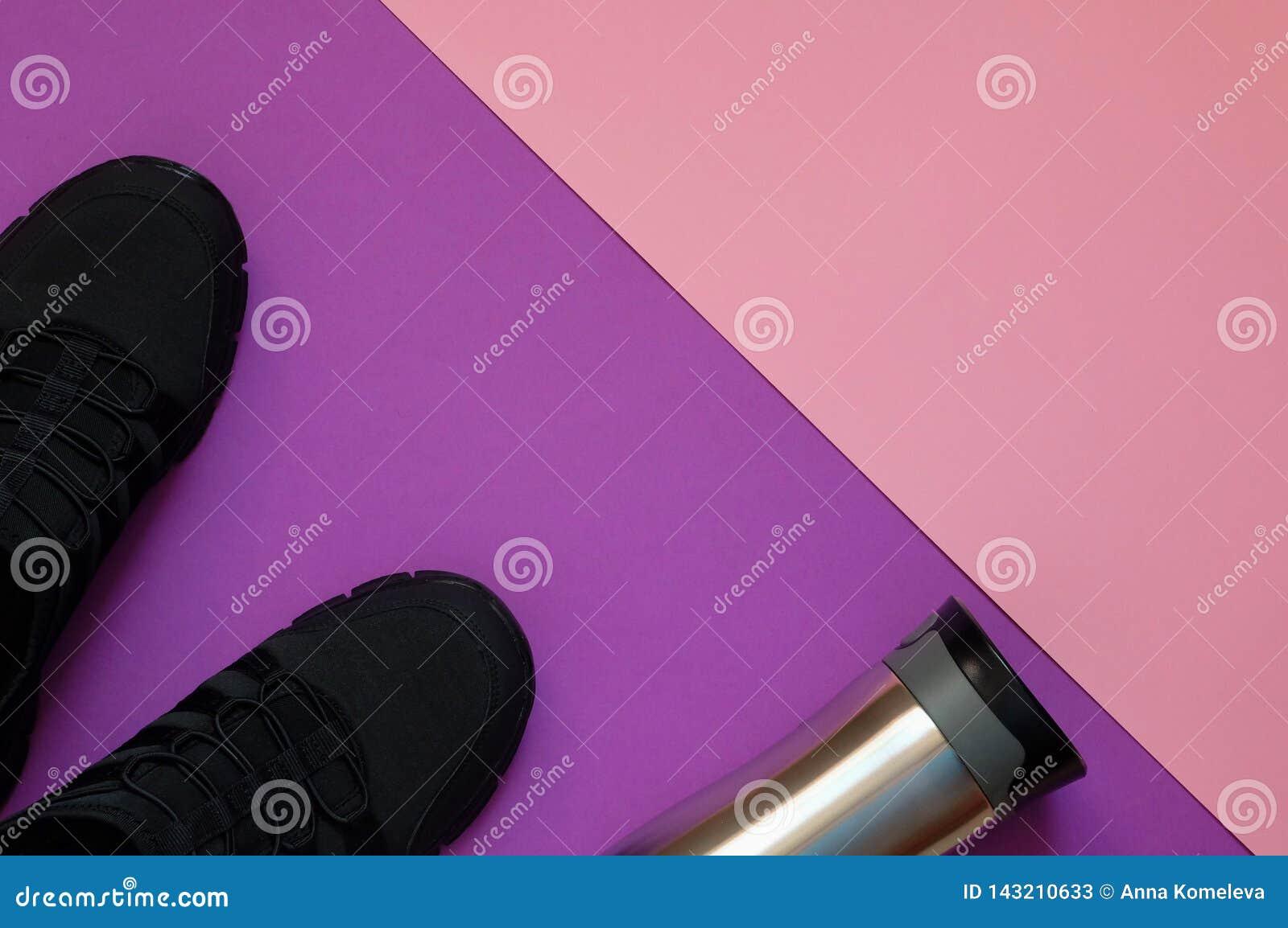 Espadrilles et bouteille noires en métal sur l espace géométrique violet et de corail de copie de whith de fond