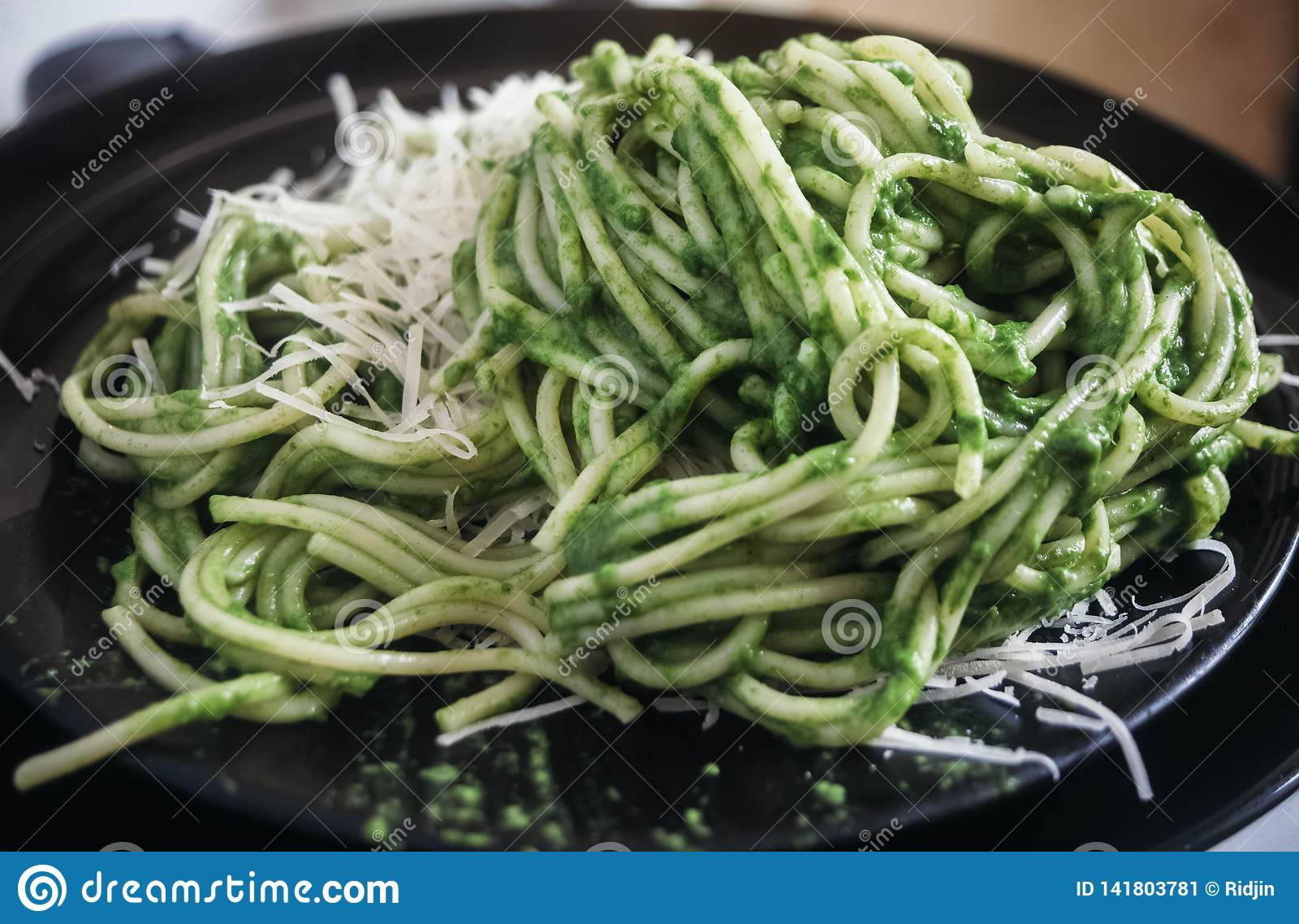 Espaguetes com molho verde da rúcula do alho e do azeite, com queijo raspado