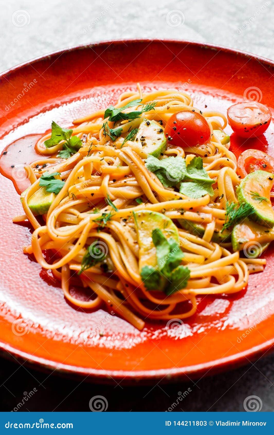 Espaguetes com tomates, avacado e abobrinha, culin?ria do vegetariano Fundo cinzento, vista superior, fim acima