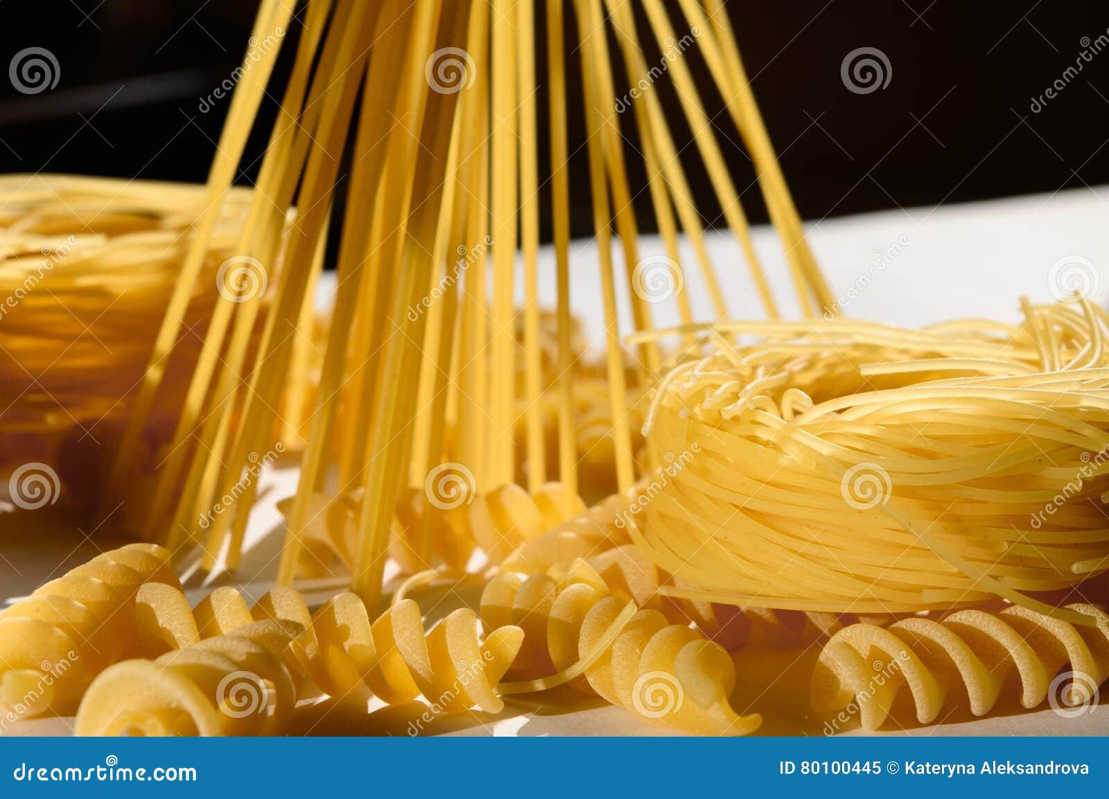 Espaguetes, massa do ninho, fusilli na luz do sol na tabela branca