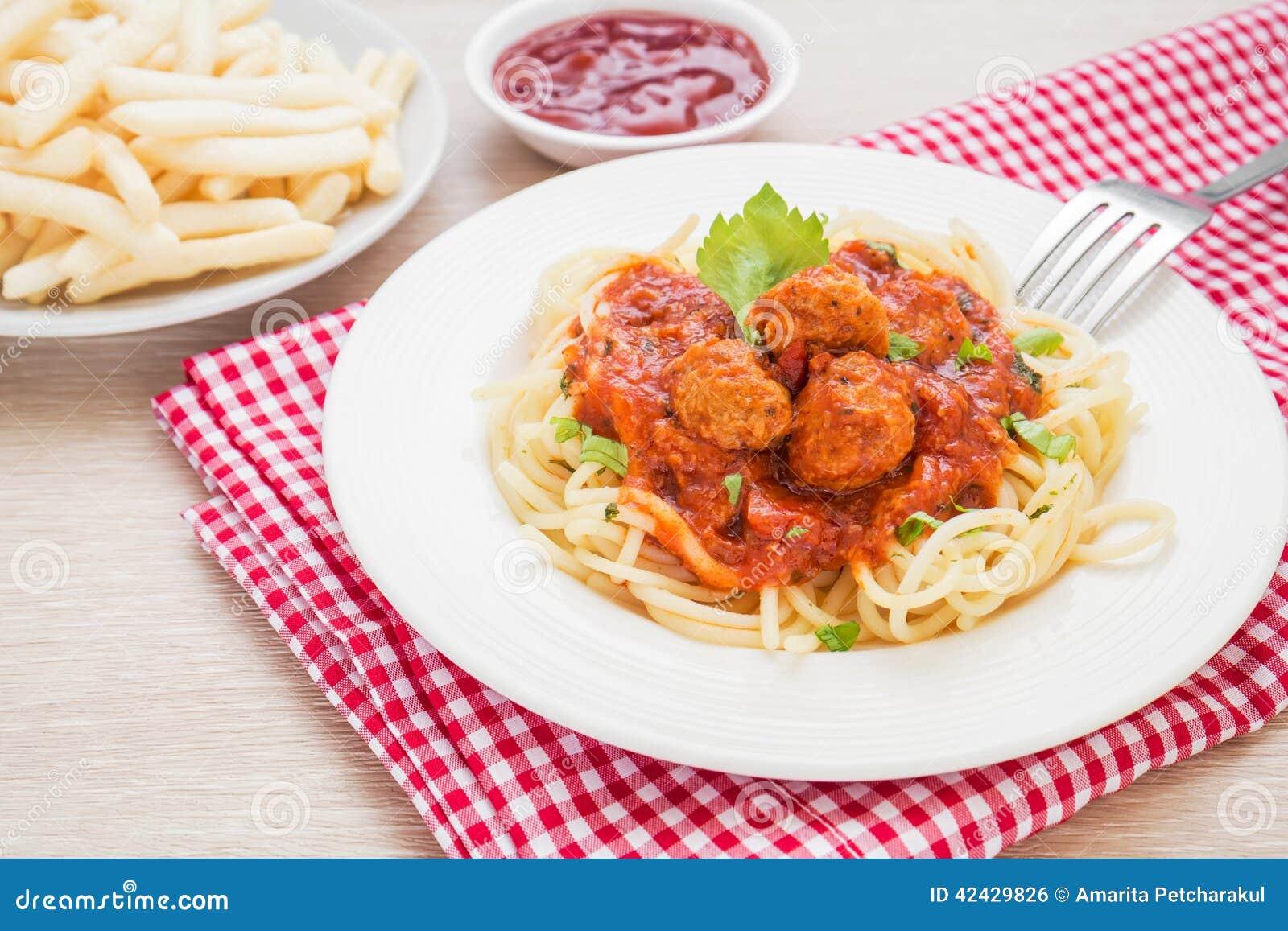 Espaguetis con las albóndigas en salsa de tomate y patatas fritas