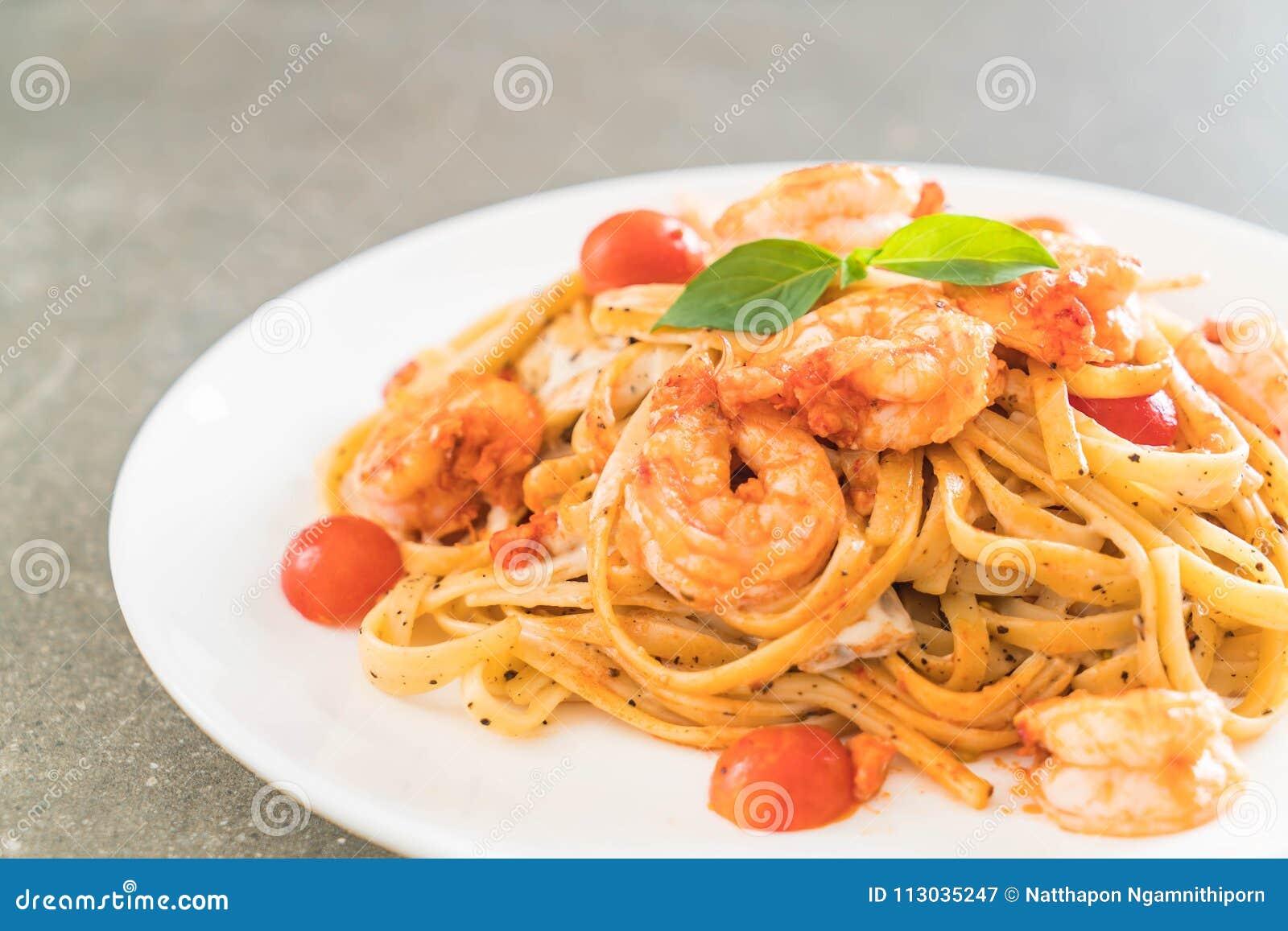 Espaguetis con los camarones, los tomates, la albahaca y el queso