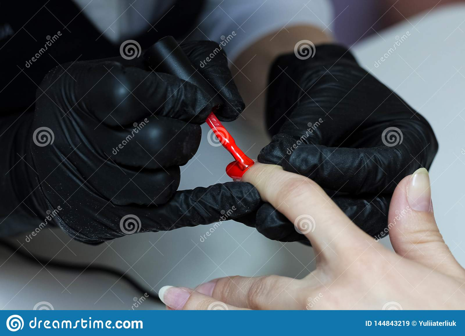 Especialista do tratamento de m?os em cuidados pretos das luvas sobre pregos das m?os O manicuro pinta pregos com verniz para as