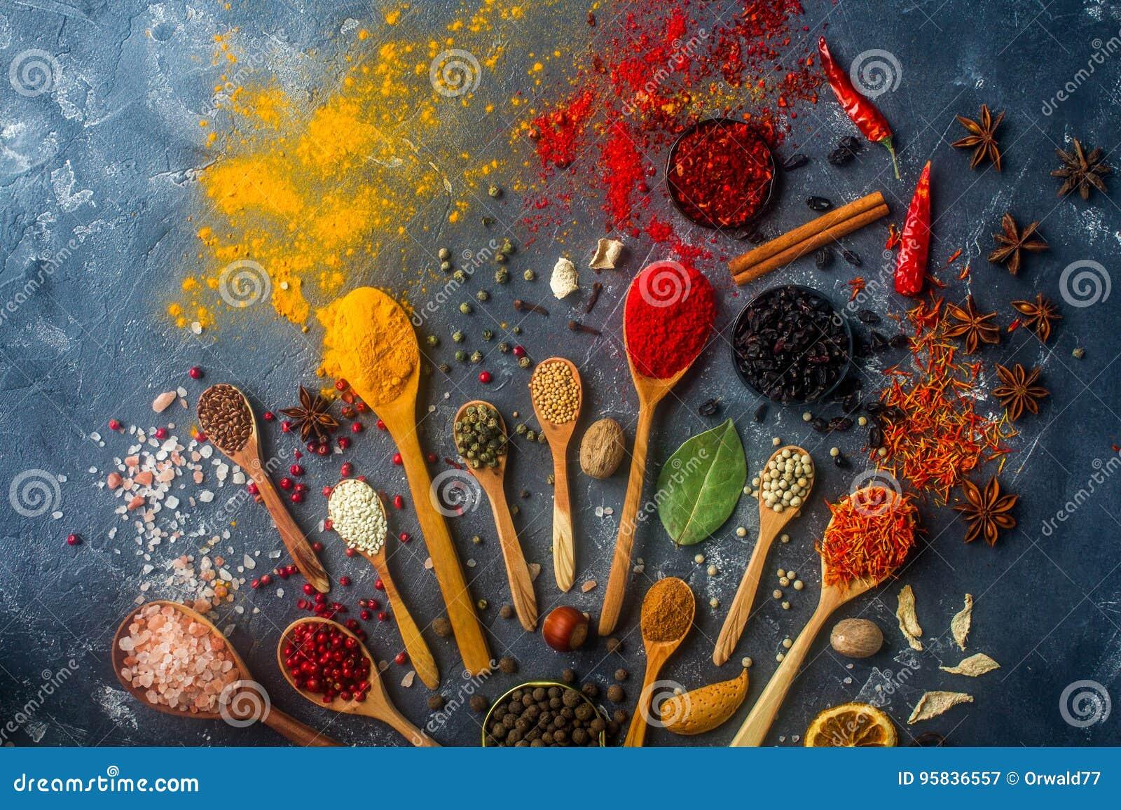 Especiarias coloridas em colheres, em sementes, em ervas e em porcas de madeira na tabela de pedra escura
