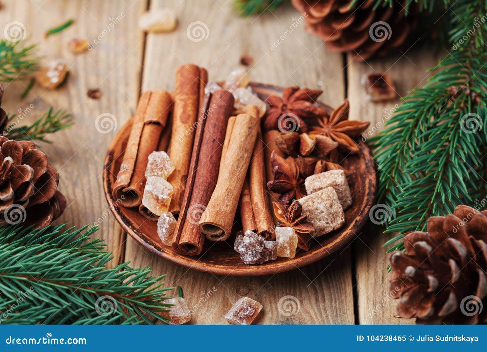 Especias de la Navidad en placa en la tabla rústica de madera Estrella del anís, palillos de canela y azúcar marrón