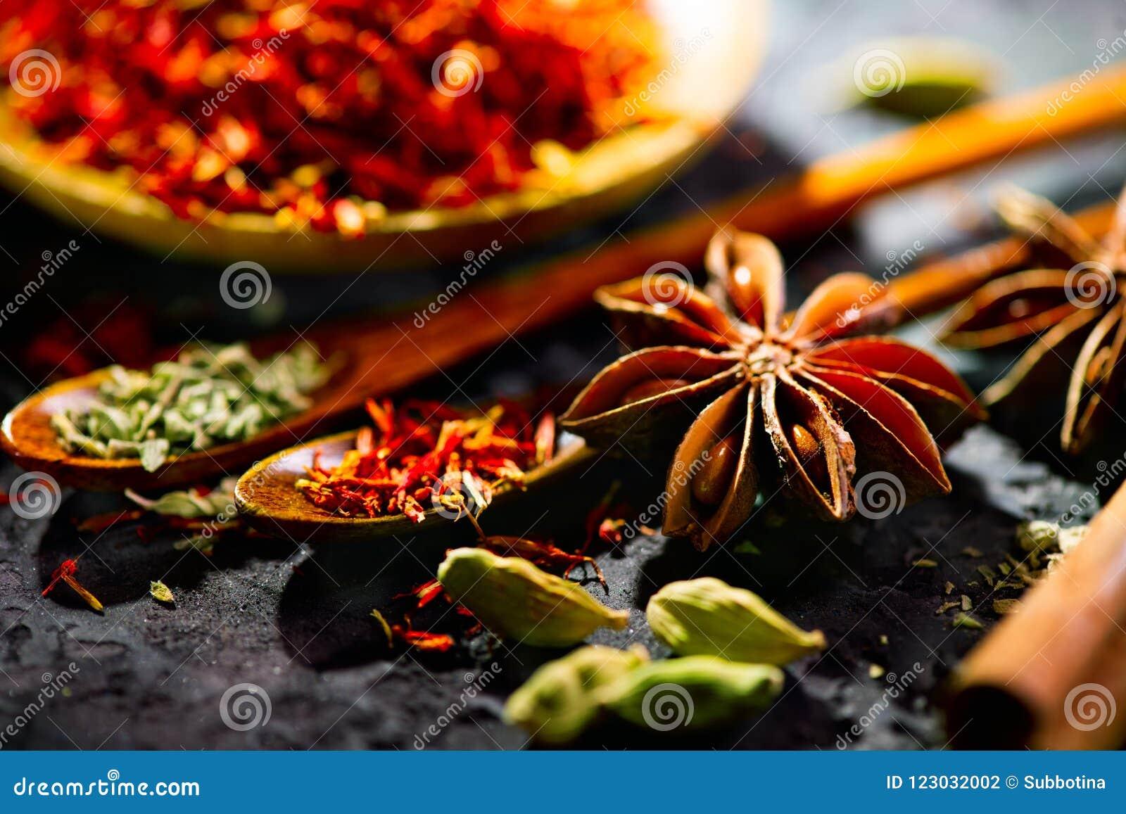 Especias Diversas especias indias en la tabla de piedra negra Especia e hierbas en fondo de la pizarra