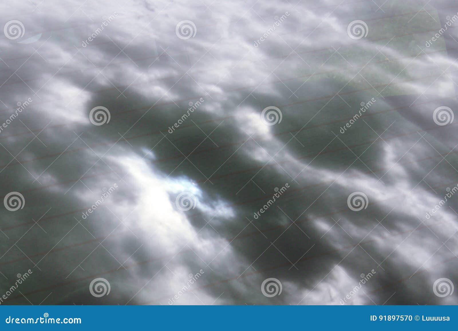 Espejo del cielo nublado de la tormenta en vidrio del coche