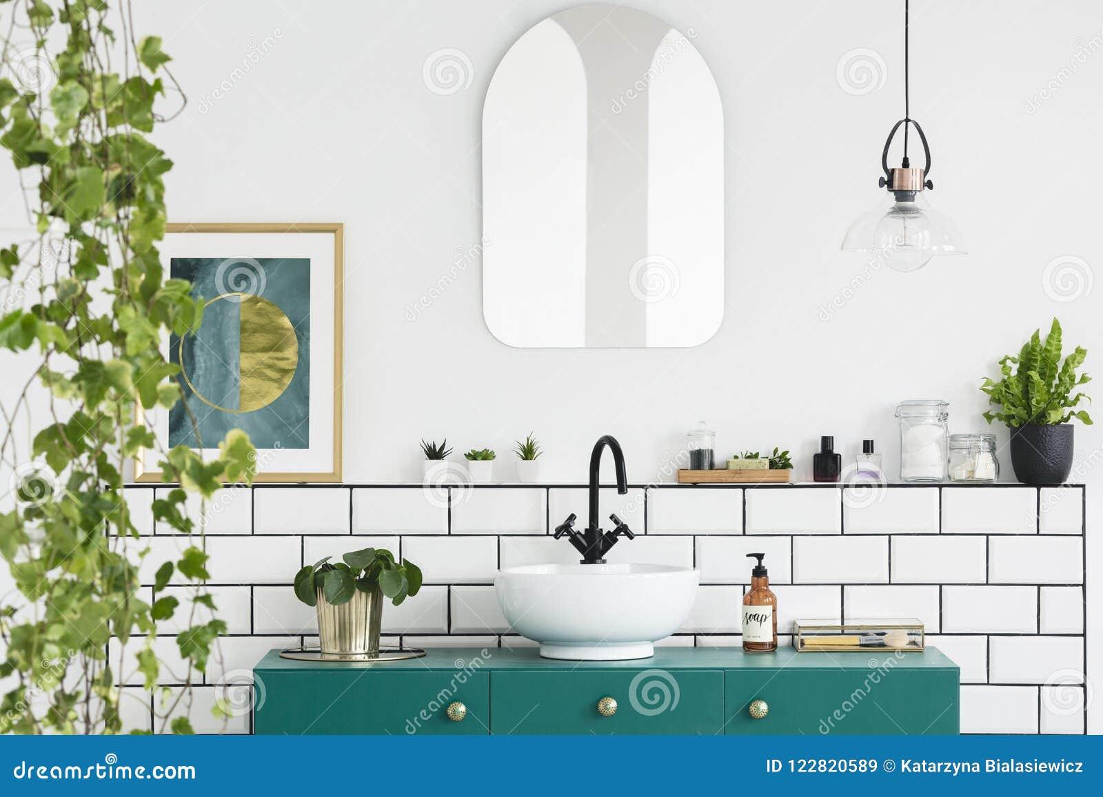 Espejo en la pared blanca sobre el lavabo verde en interior del cuarto de baño con las plantas y el cartel Foto verdadera