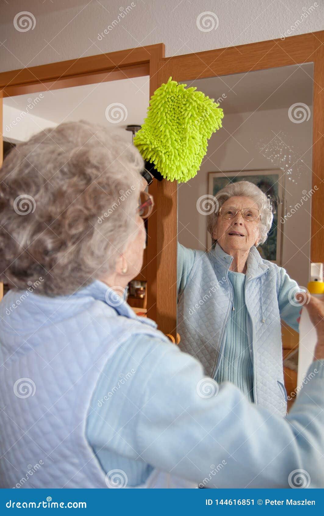 Espejo mayor de la limpieza de la mujer en casa