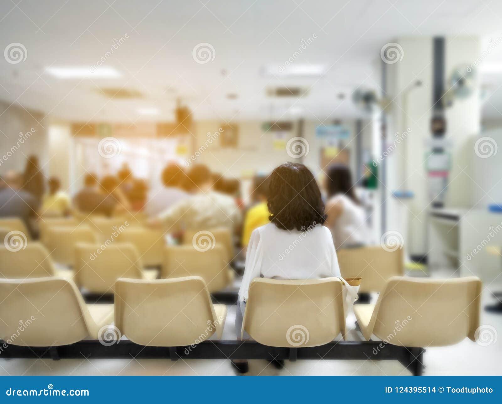 Espera da jovem mulher e dos muitos povos médica e serviços sanitários ao hospital, pacientes que esperam o tratamento no hospita