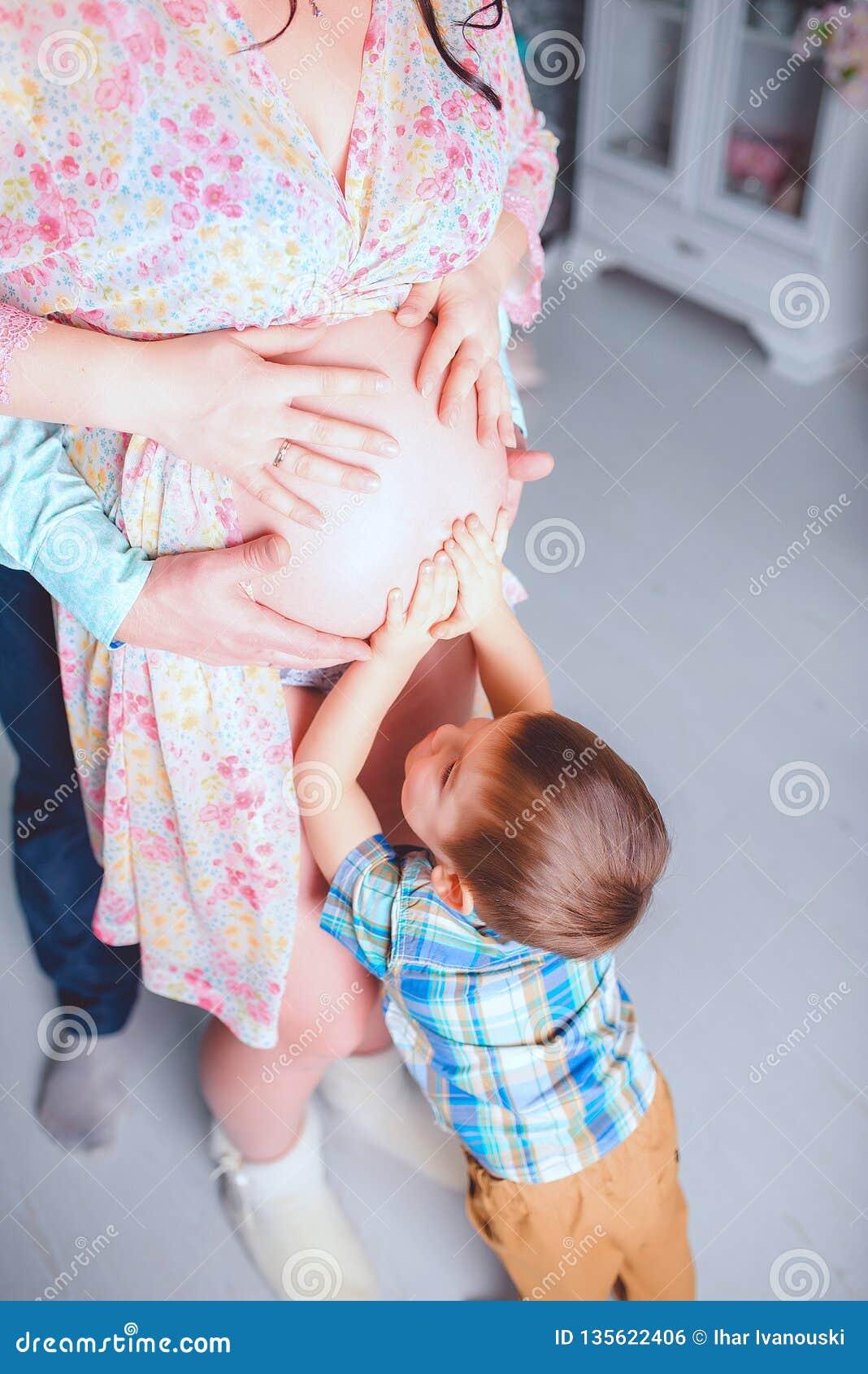 Esperando sua irmã, o menino toca em sua barriga