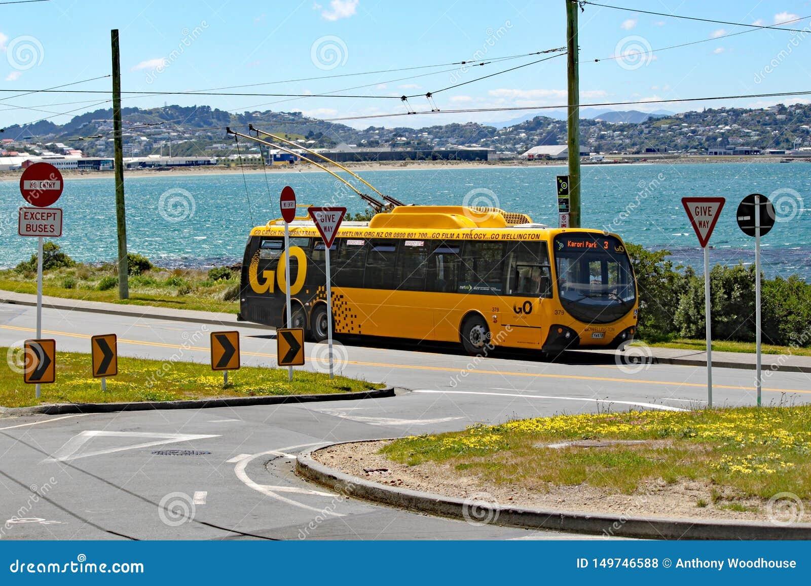 Esperas eléctricas amarillas de un autobús en el término por el lado de la bahía de Lyall, Wellington, Nueva Zelanda