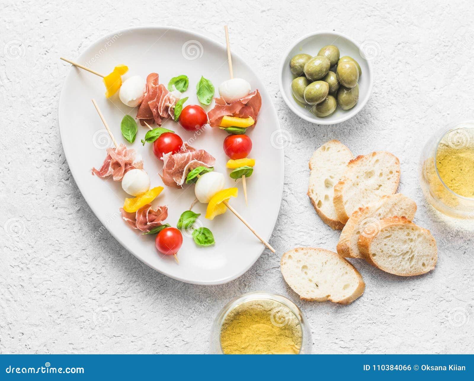 Espetos do Antipasto Aperitivo mediterrâneo a wine - prosciutto, pimentas de sino, tomates de cereja, mozzarella em espetos e w