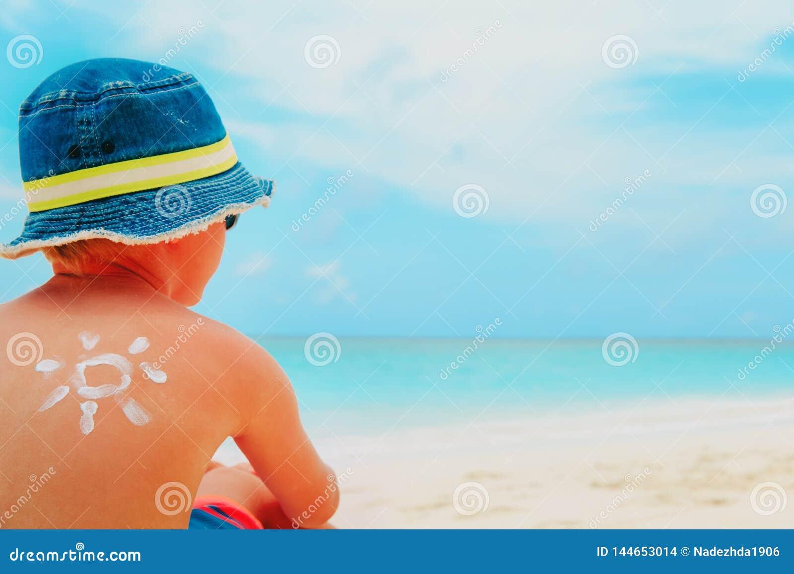 Esponga al sole il ragazzino della protezione con suncream alla spiaggia tropicale