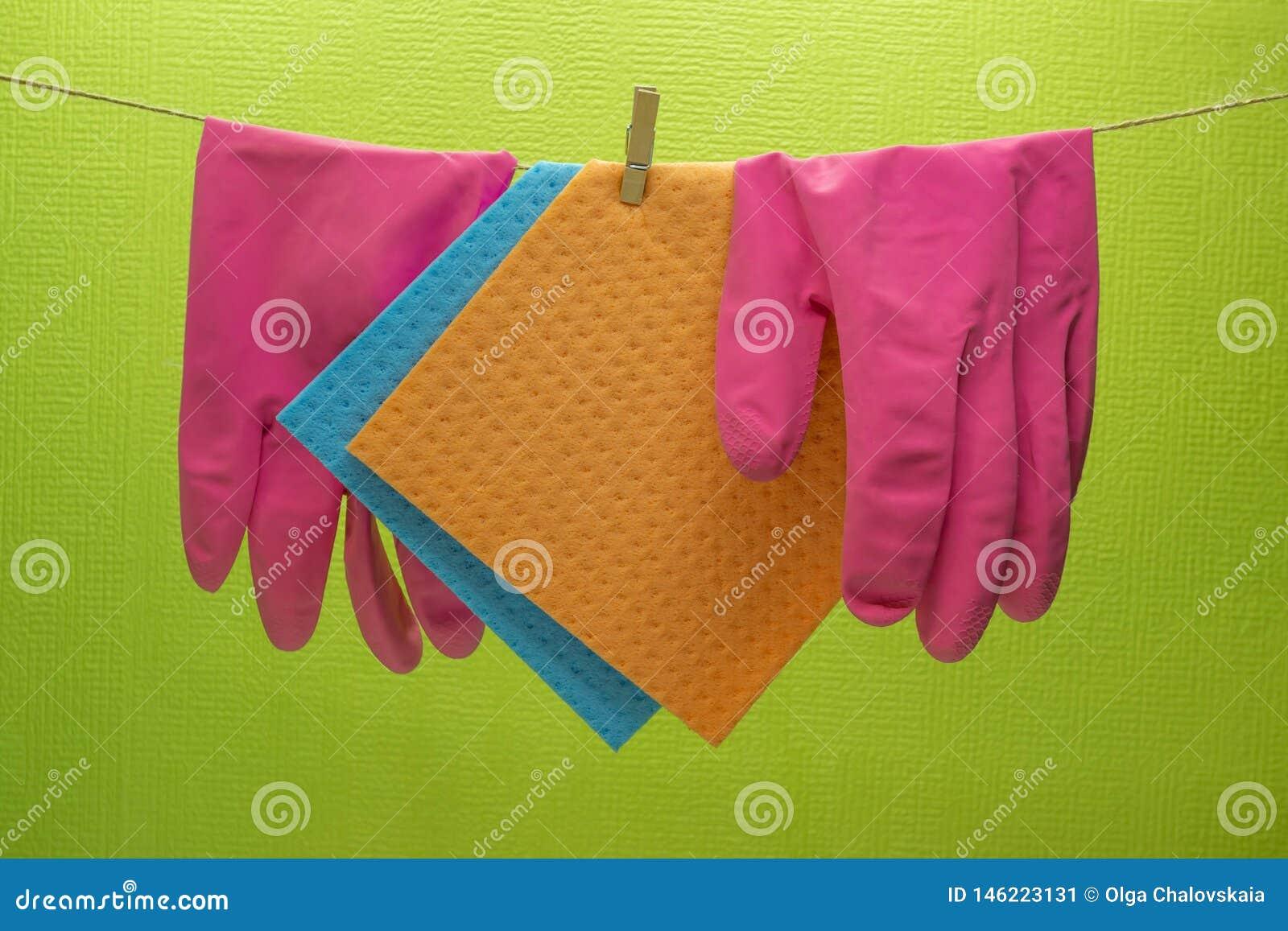 Esponjas da cozinha e luvas de borracha que penduram na corda