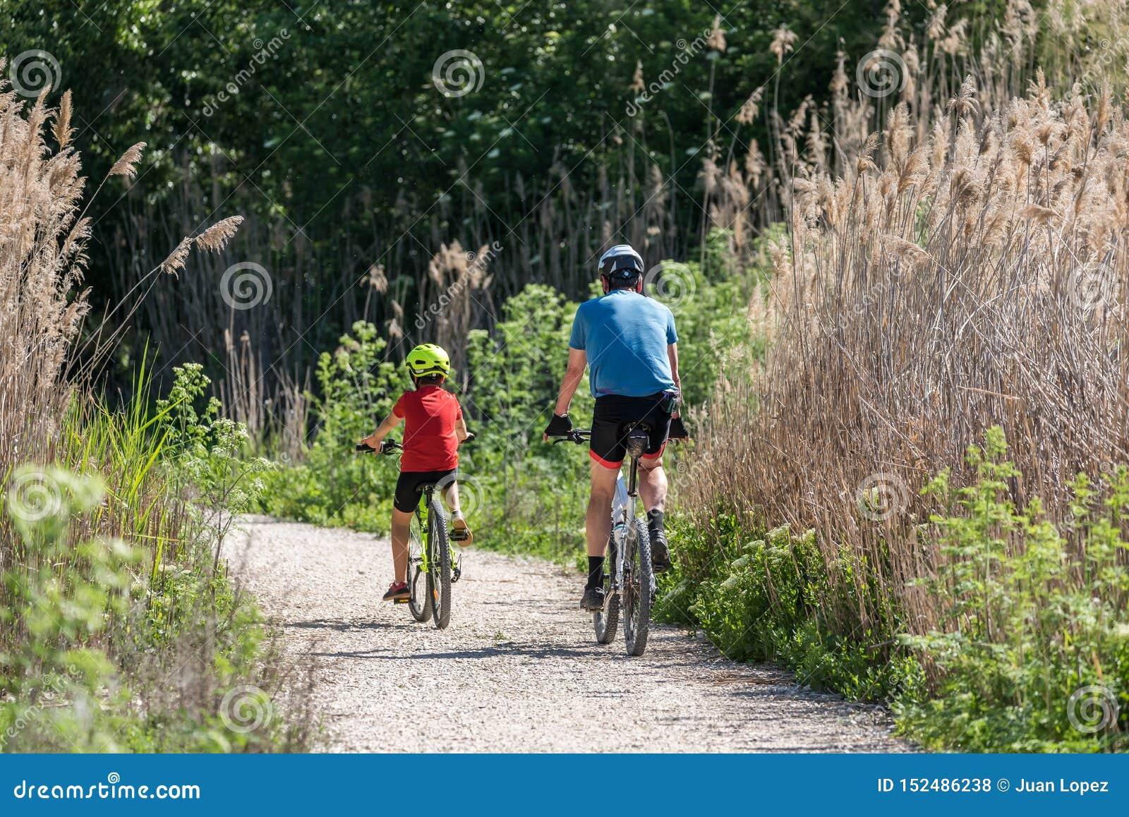 Esporte praticando do pai e do filho pela bicicleta