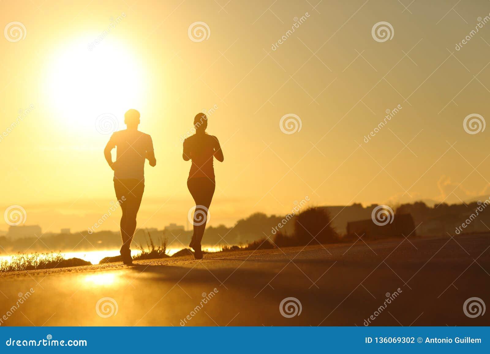 Esporte praticando dos pares que corre no por do sol na estrada