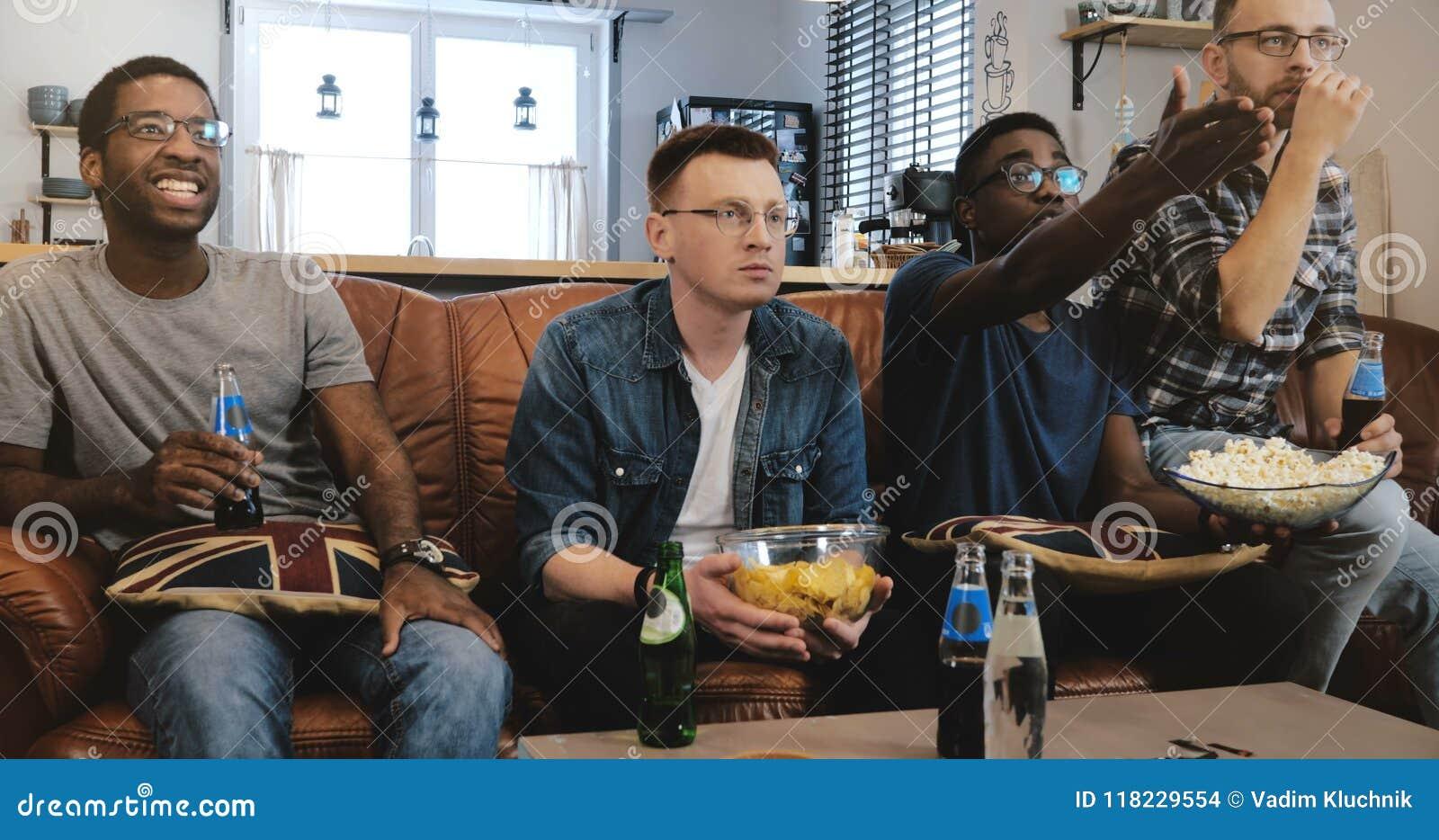 Esportes masculinos afro-americanos do relógio dos amigos na tevê Multi fãs geeky étnicos concentrados e sérios no sofá com pipoc