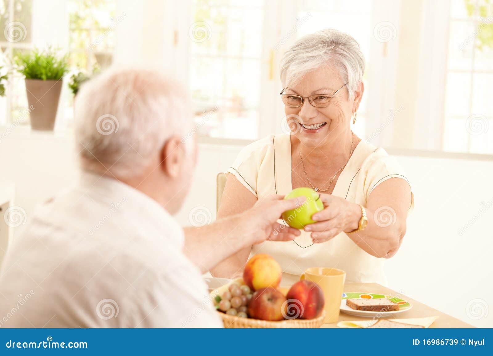Esposa mayor de risa que consigue la manzana de marido